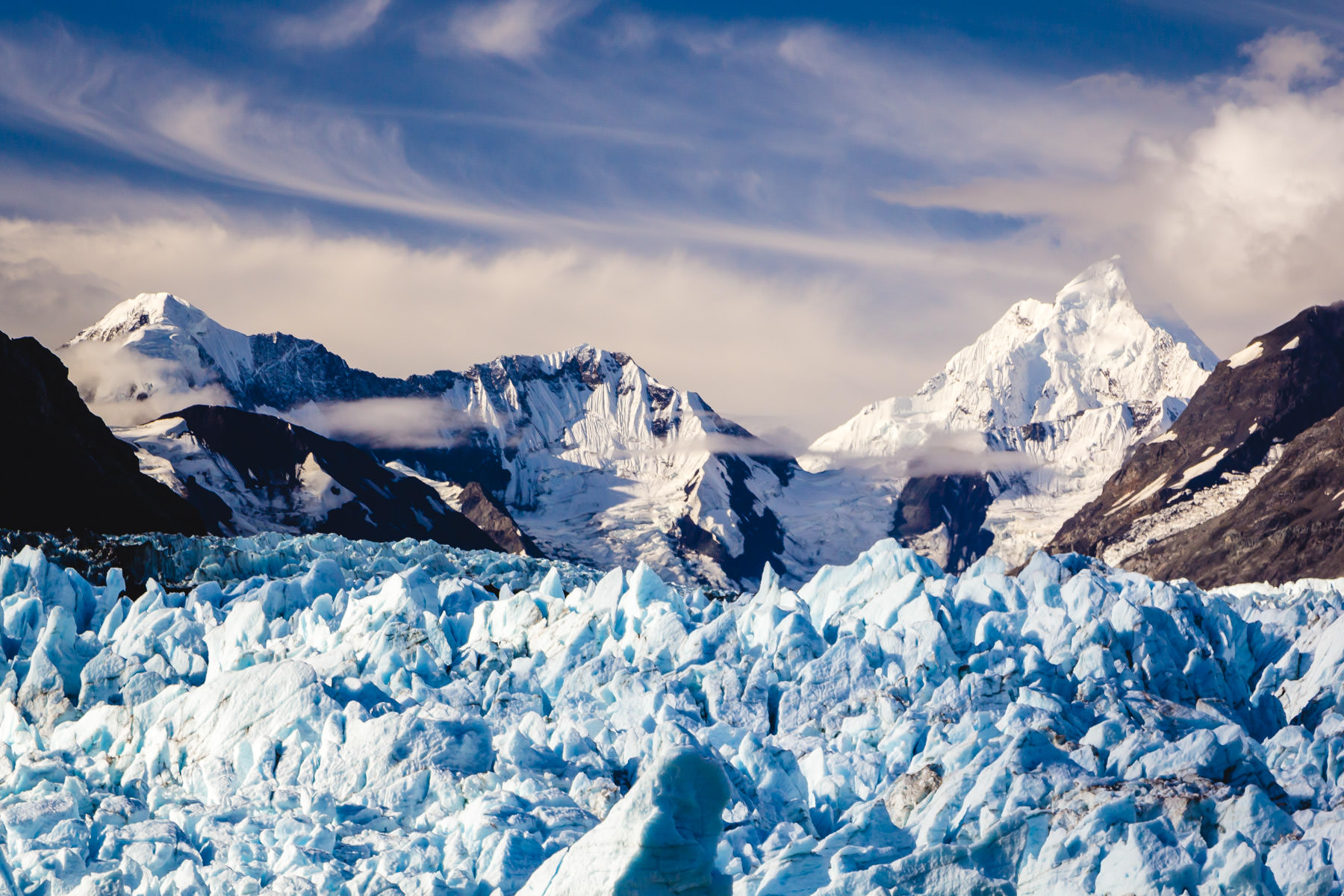 Mountains rise over the Margerie Glacier at Glacier Bay National Park, Alaska.