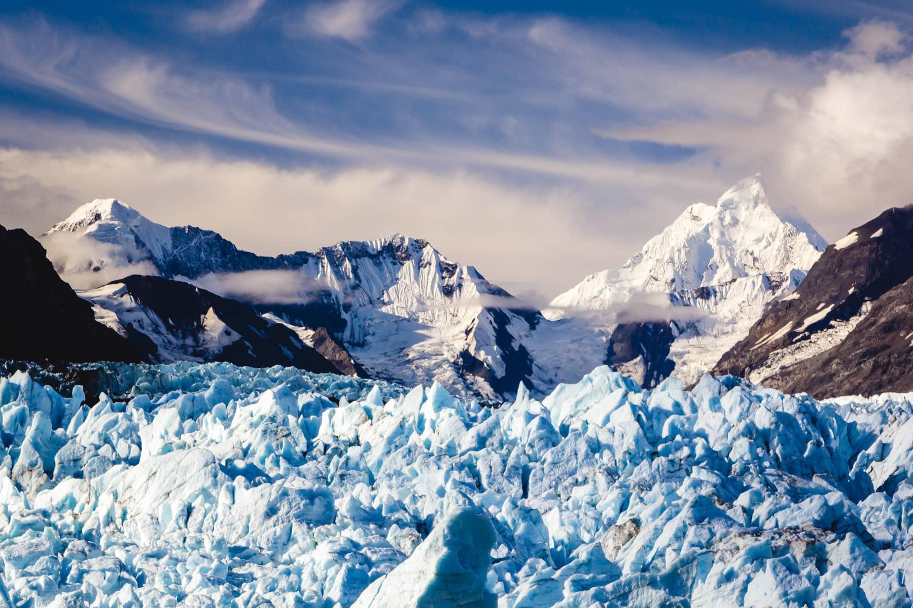 Mountains rise over the Margerie Glacier at Glacier Bay National Park, Alaska.