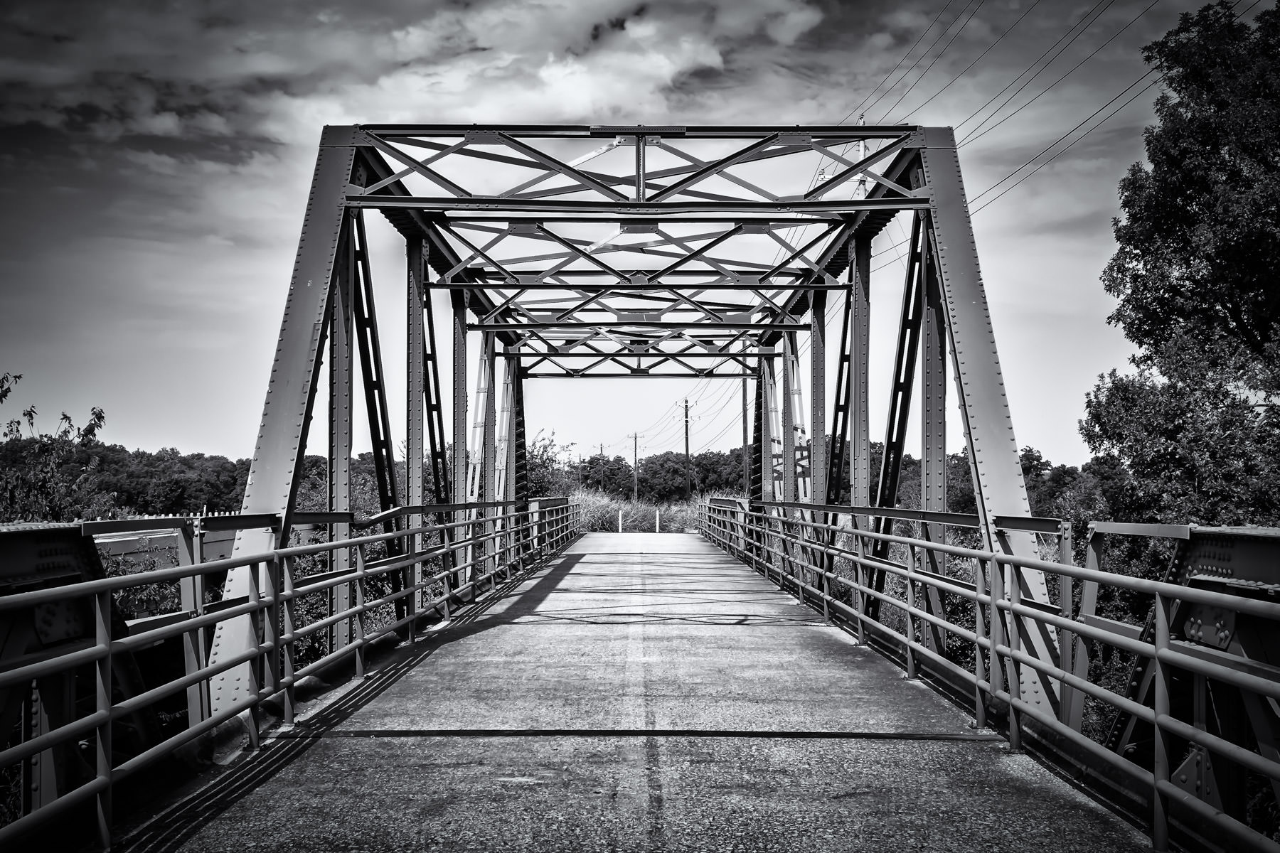 An iron pedestrian bridge spans the Elm Fork of the Trinity River near Aubrey, Texas.