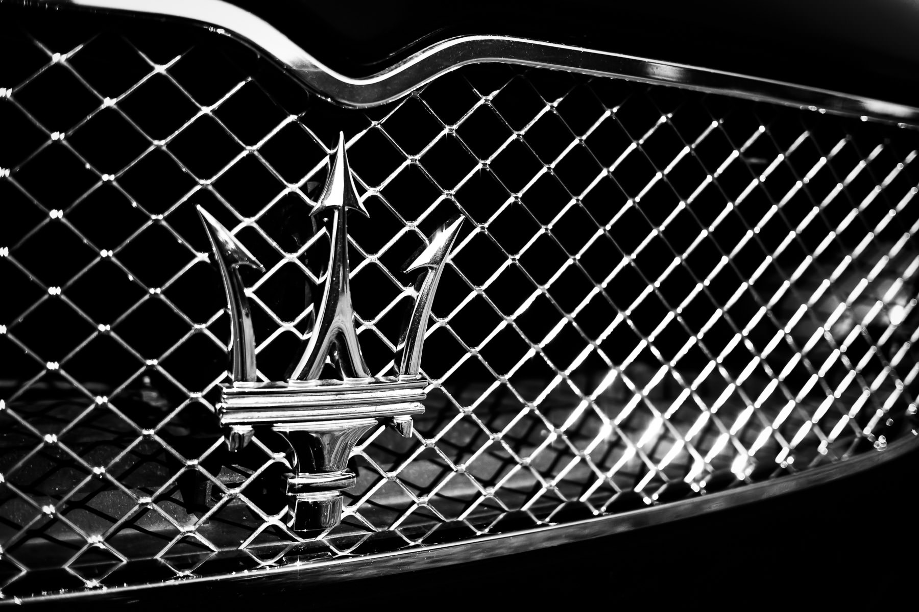 Detail of a Maserati's grille-mounted trident emblem at ItalianCarFest in Grapevine, Texas.