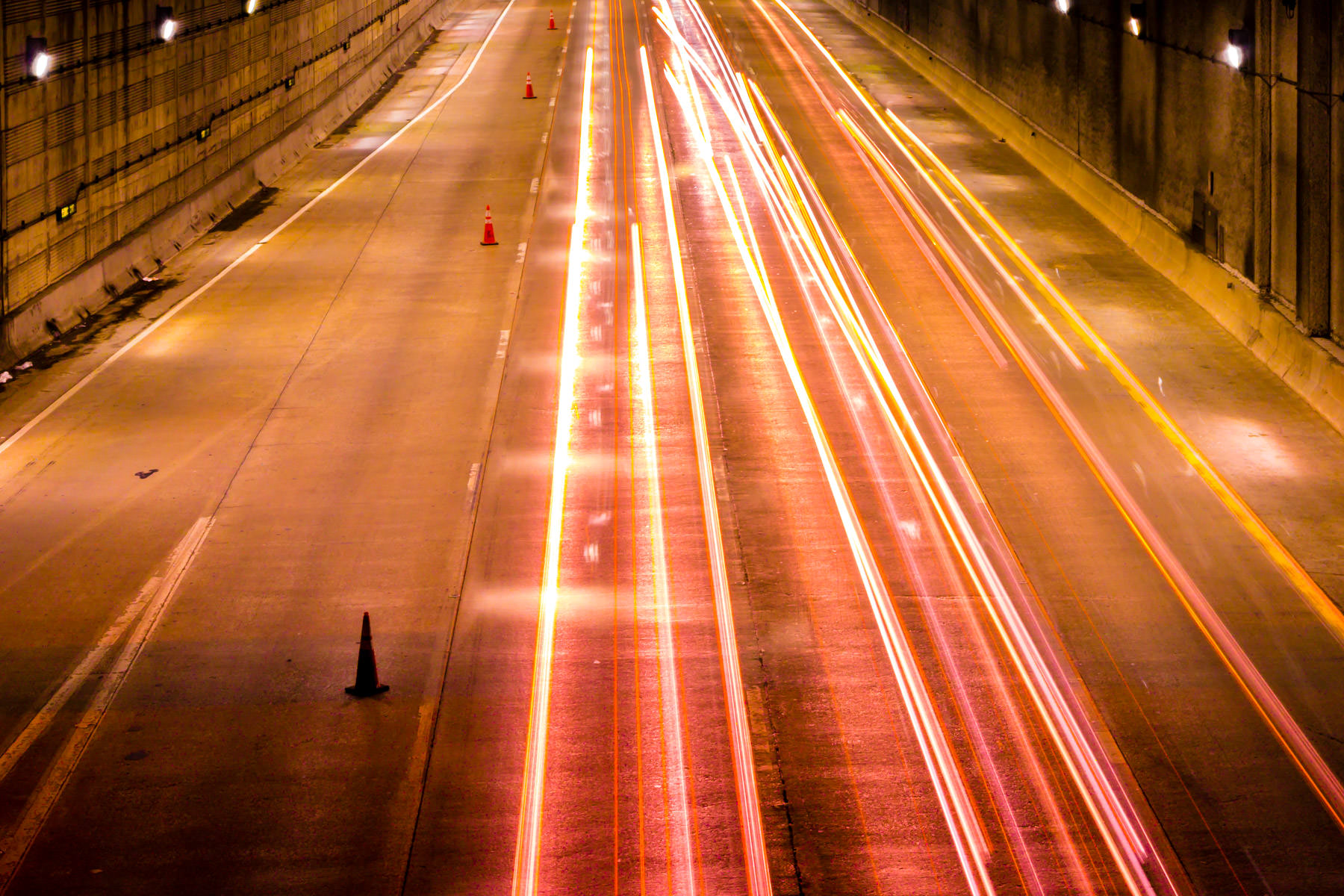 Car lights leave light trails on Woodall Rogers Freeway as they speed under the 1,200-foot-long deck that supports Dallas' Klyde Warren Park.