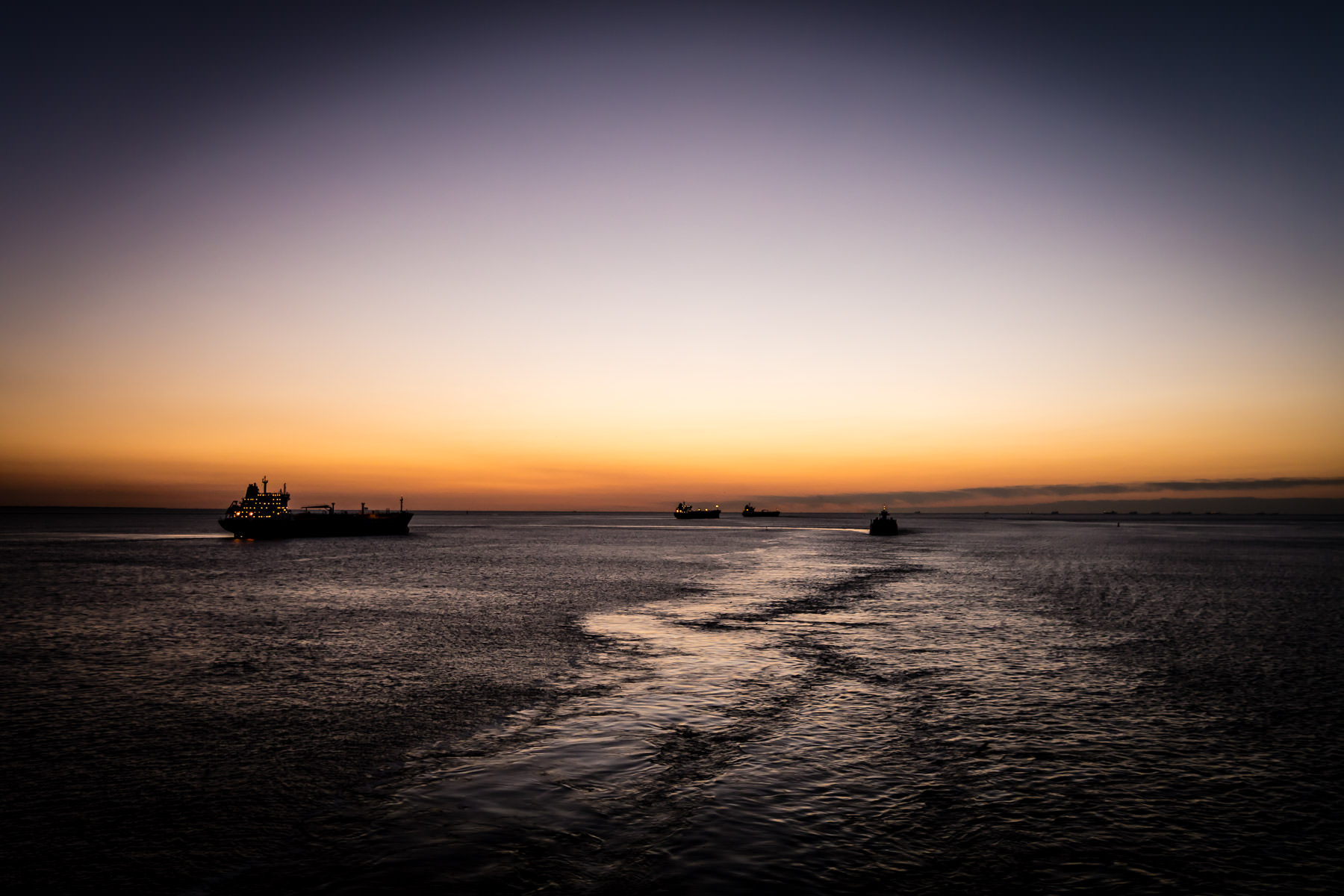 Ships transit Bolivar Roads just off the coast of Galveston, Texas, as the sun rises over the Gulf of Mexico.