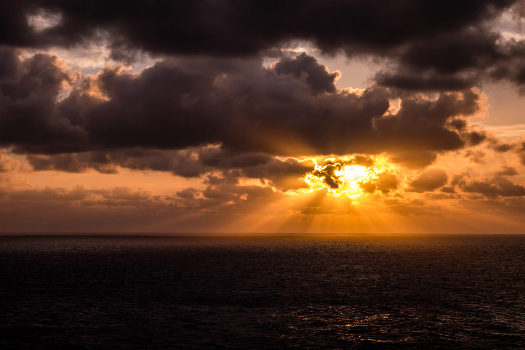 The sun's rays pierce the morning clouds to illuminate the Gulf of Mexico.