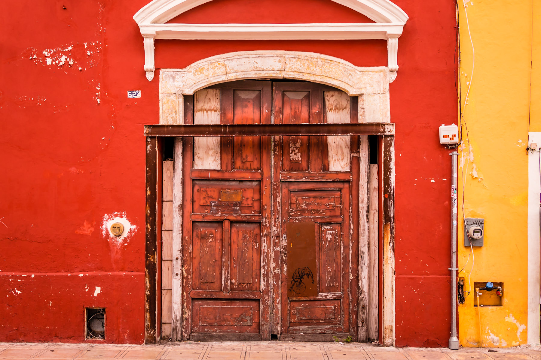 An aged door on a brightly-colored building in Mérida, Yucatán, Mexico.