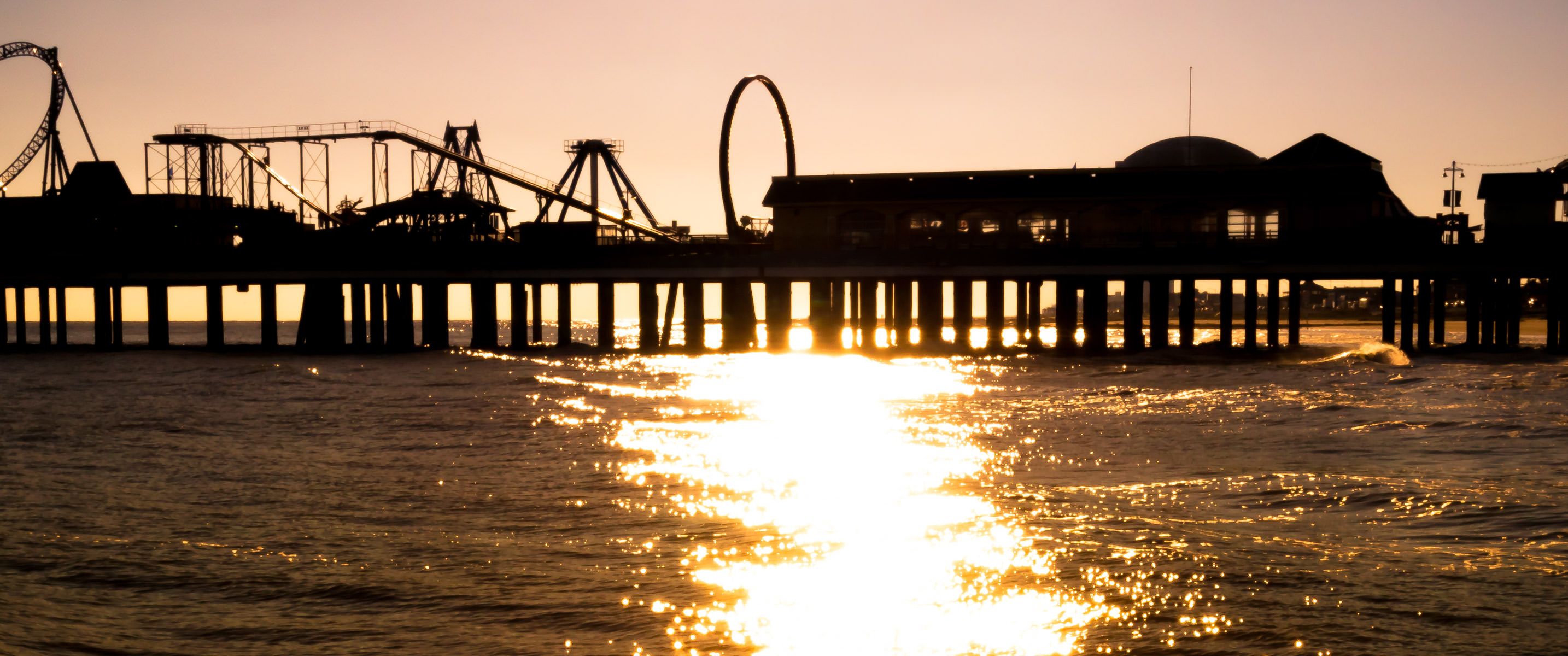 Galveston, Texas' Historic Pleasure Pier is silhouetted by the late-afternoon sun over the Gulf of Mexico.