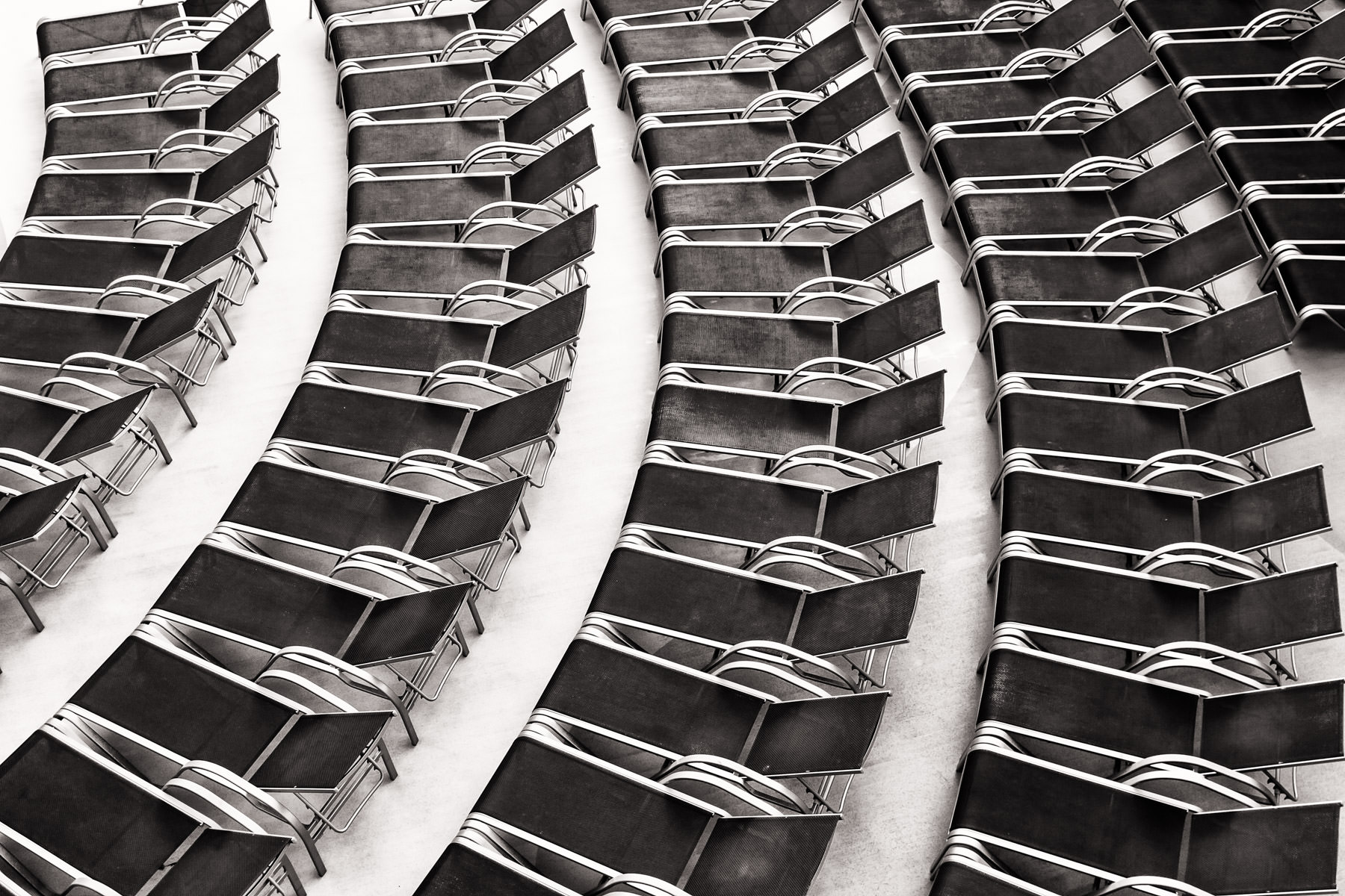 Deck chairs arranged in arcs await guests aboard the cruise ship Carnival Magic.