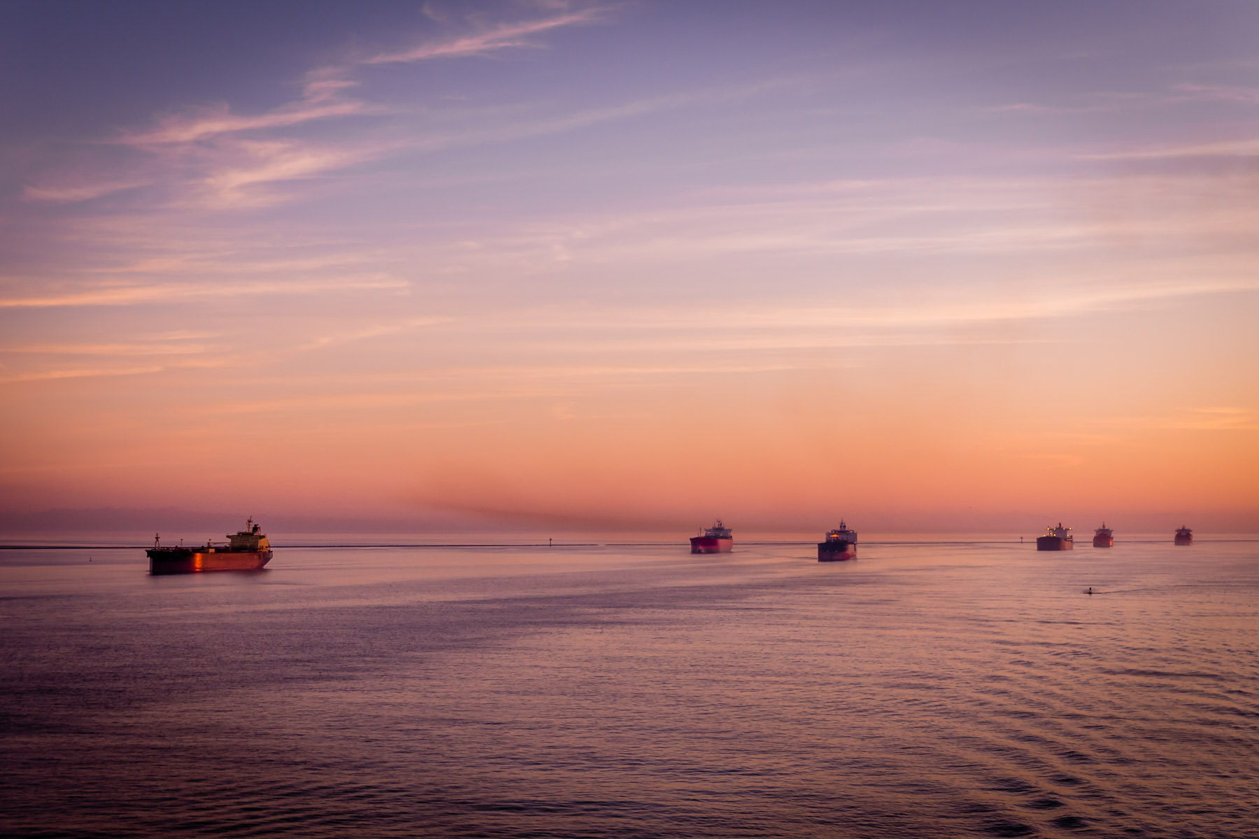 Tankers await their turn to enter the Port of Houston as the sun rises over the Gulf of Mexico just off the shore of Galveston, Texas.