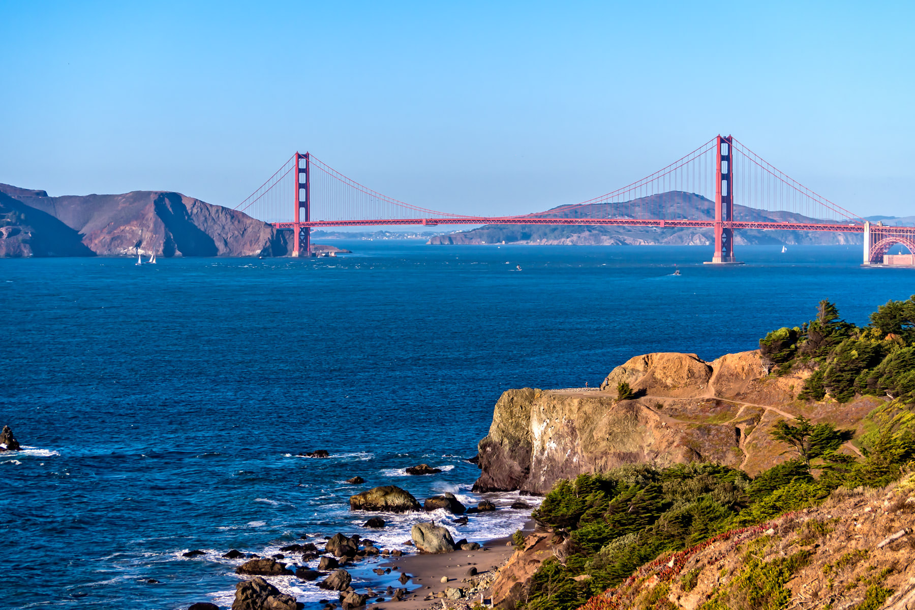 The iconic Golden Gate Bridge spans the entrance to San Francisco Bay as seen from the cliffs of the Coastal Trail at Lands End.