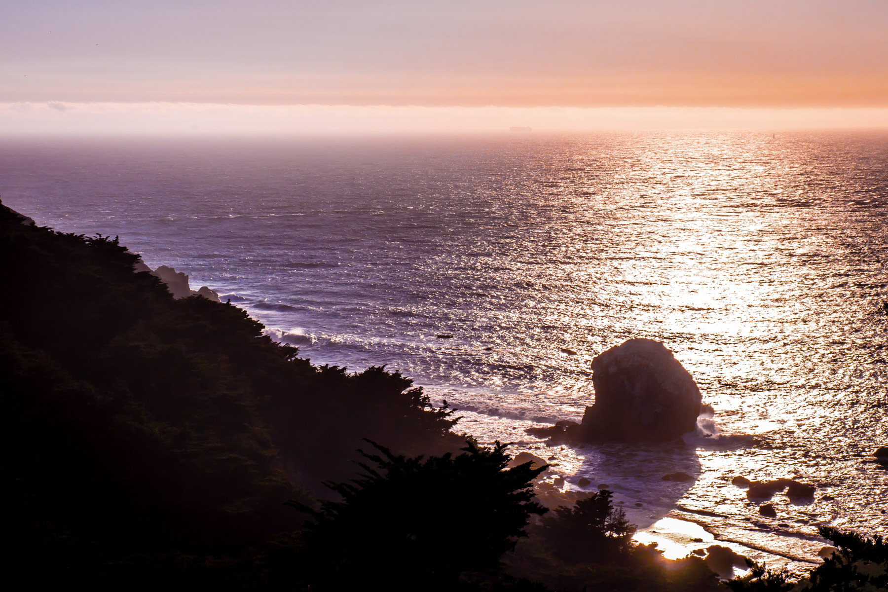 The late-evening sun silhouettes the rocky tree-covered Pacific Ocean shoreline of San Francisco's Lands End on the western edge of the city.