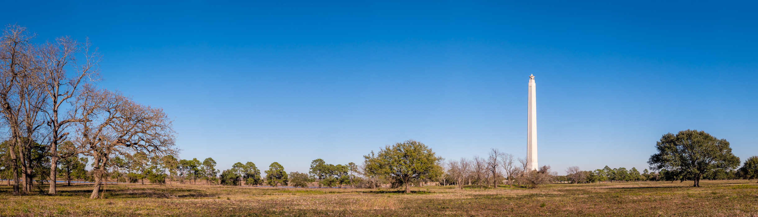 "A panoramic view of the San Jacinto Battleground—the site of the decisive battle of the Texas Revolution on April 21, 1836, that ensured Texas' independence from Mexico. The site is marked by the 567-foot-tall San Jacinto Monument, completed in 1939 and topped by a 220-ton, 34-foot ""Lone Star""."