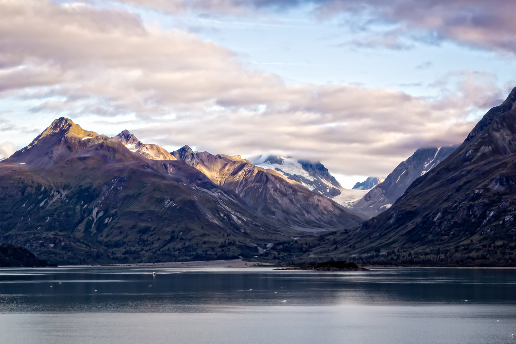 Morning clouds begin to burn off as the late-summer sun warms the mountains of Alaska's Glacier Bay.