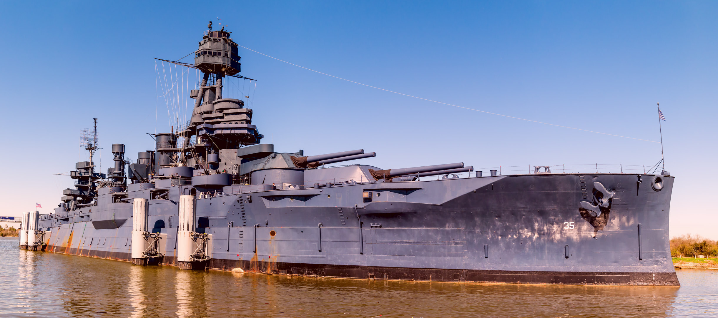 "The battleship USS Texas, nicknamed ""The Mighty T"", sits in her berth as a museum ship near Houston."