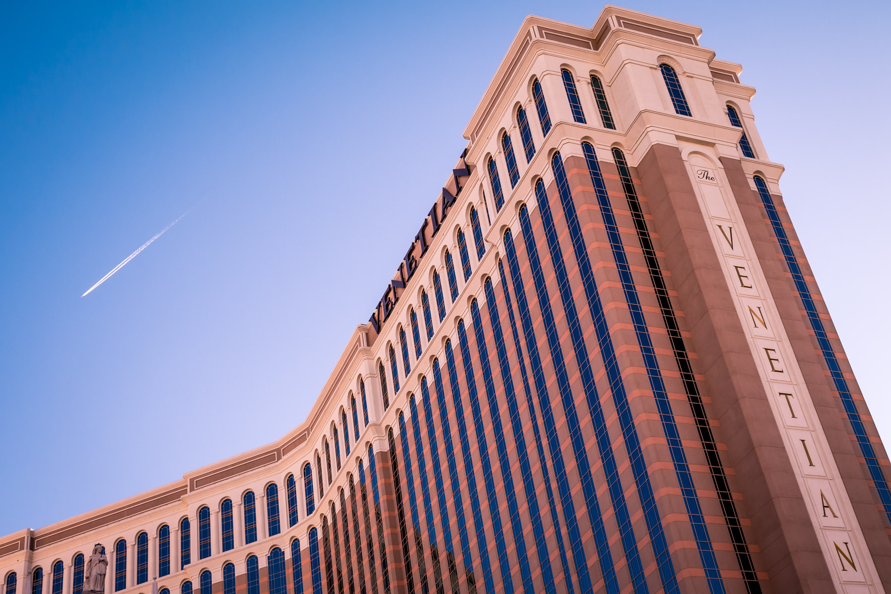 A high-flying jet leaves a contrail over Las Vegas' Venetian Hotel and Casino.
