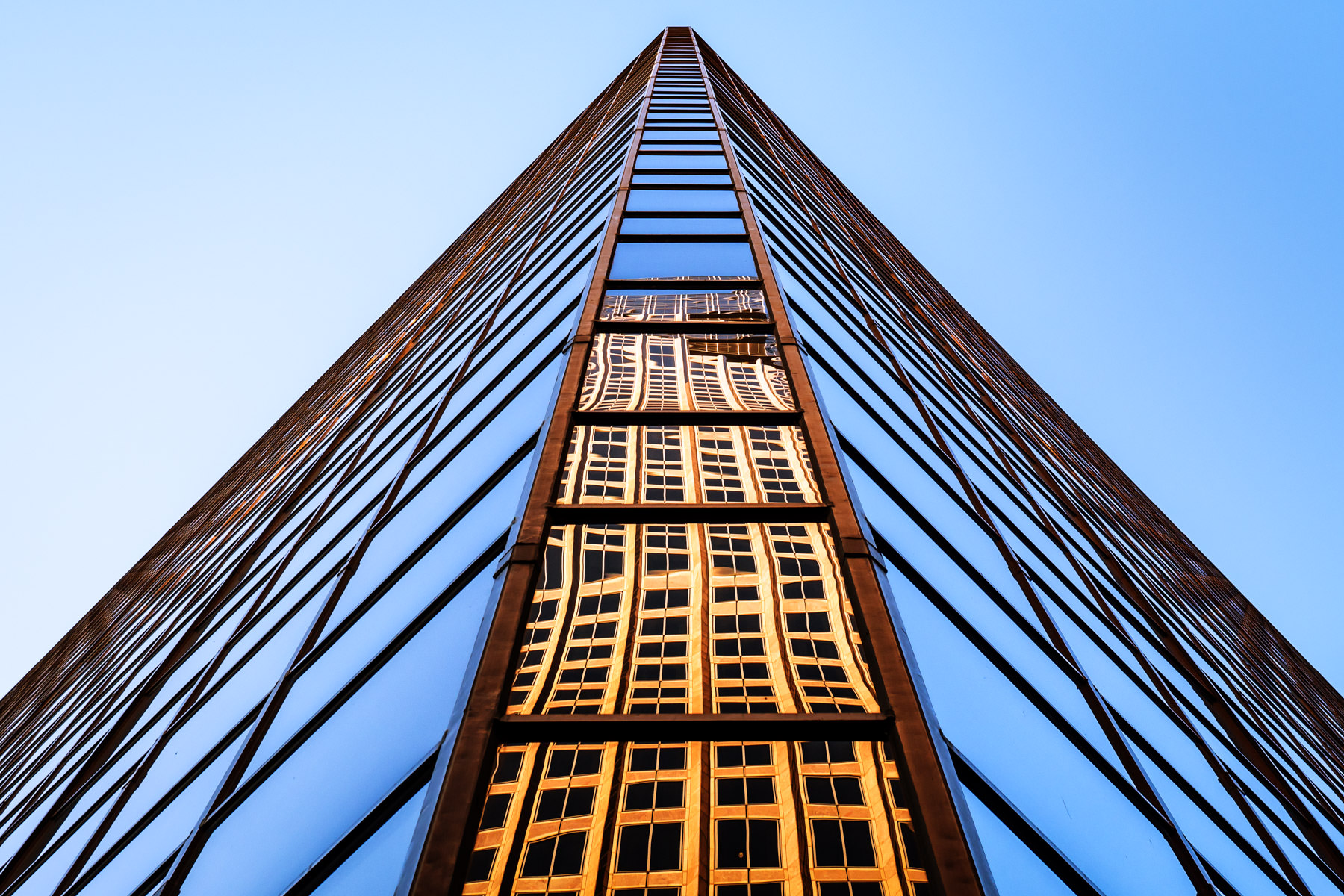 Downtown Dallas' Chase Tower is reflected in the windows of the north tower of the adjacent Plaza of the Americas.