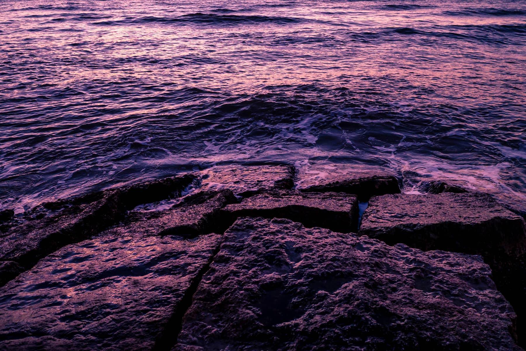 The Gulf of Mexico surf crashes onto granite blocks as the sun rises on the Galveston Island beach, Texas.