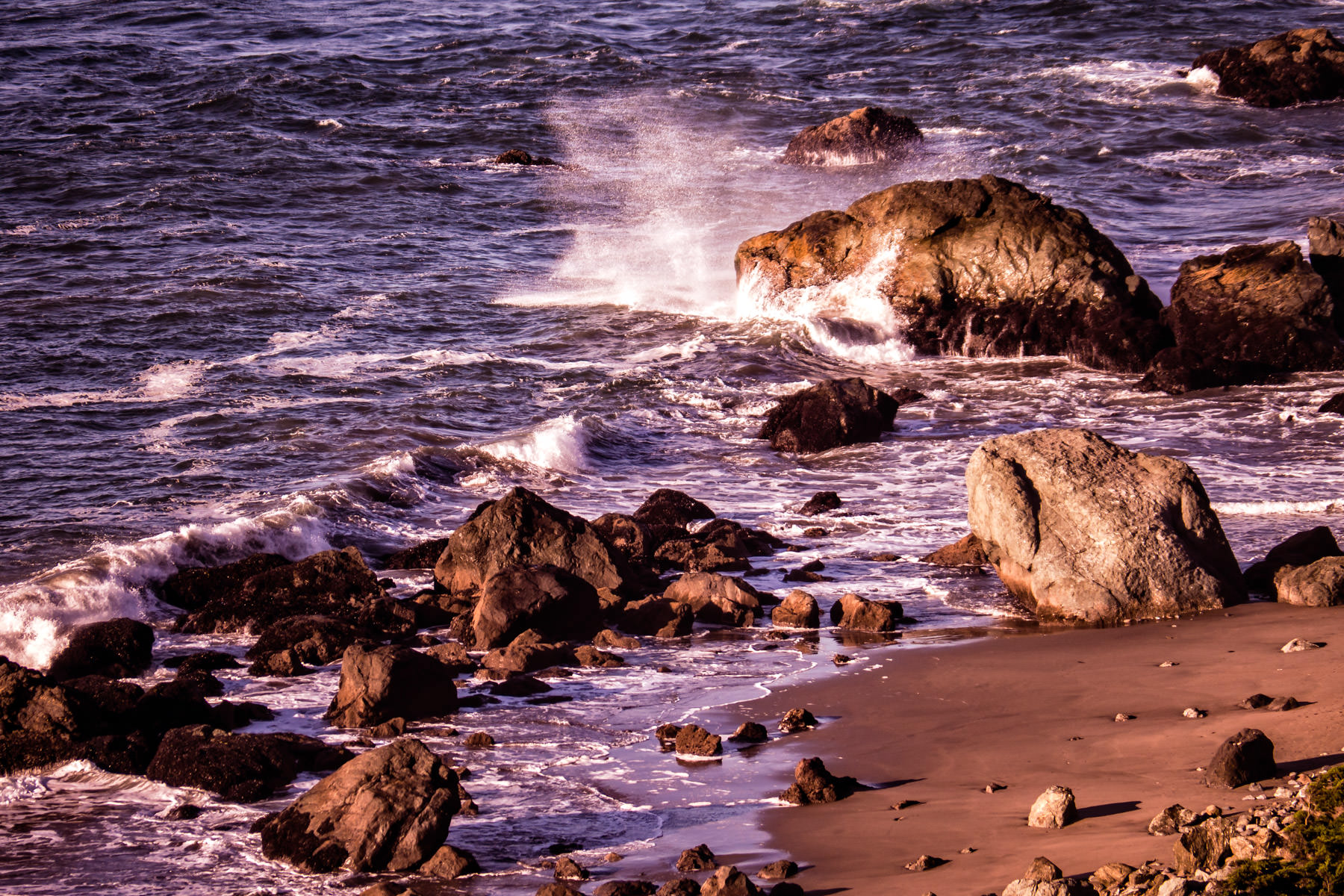 Waves crash onto rocks as the evening sun illuminates the beach at San Francisco's Lands End.