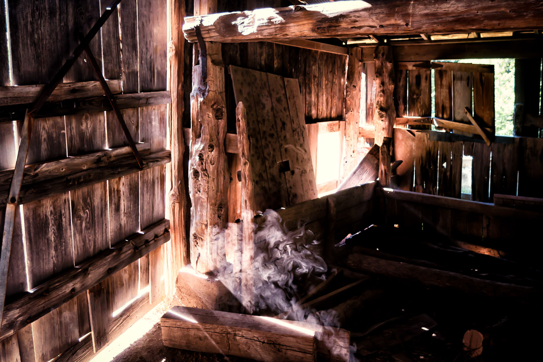 Sun spills through gaps in the wooden walls of a dilapidated barn at Penn Farm, Cedar Hill State Park, Texas.