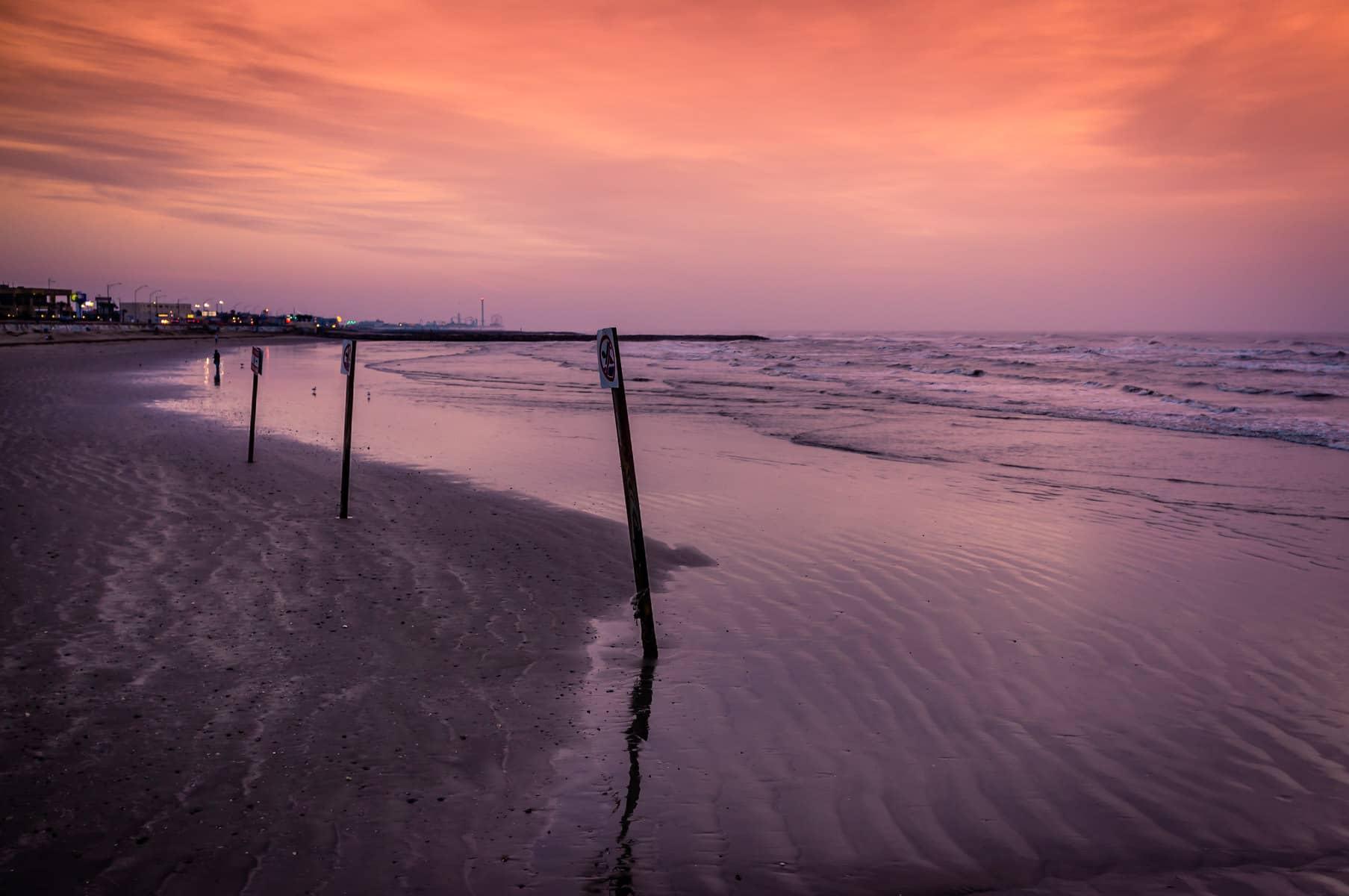The early-morning sun begins to light up Galveston, Texas' beach on an overcast day.