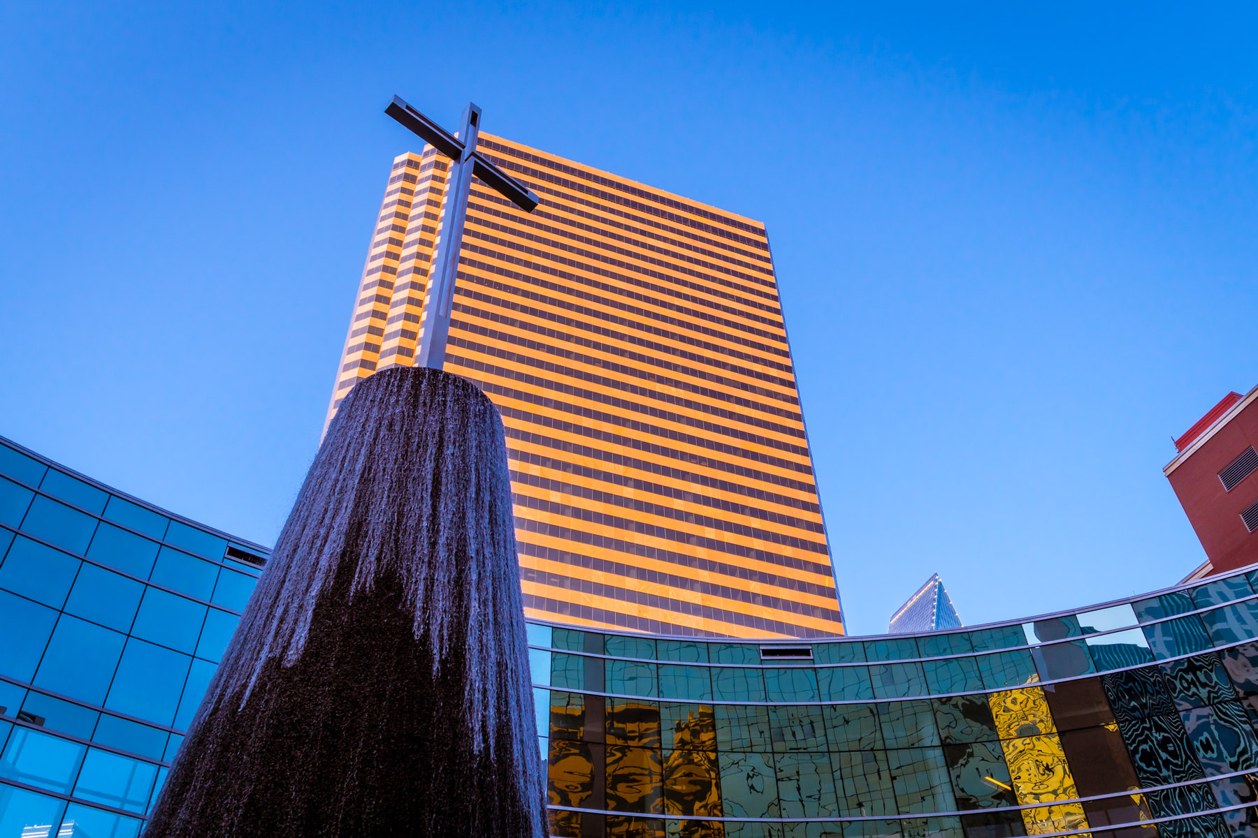A cross topping a fountain at Dallas' First Baptist Church is overshadowed by the 45-story Lincoln Plaza.