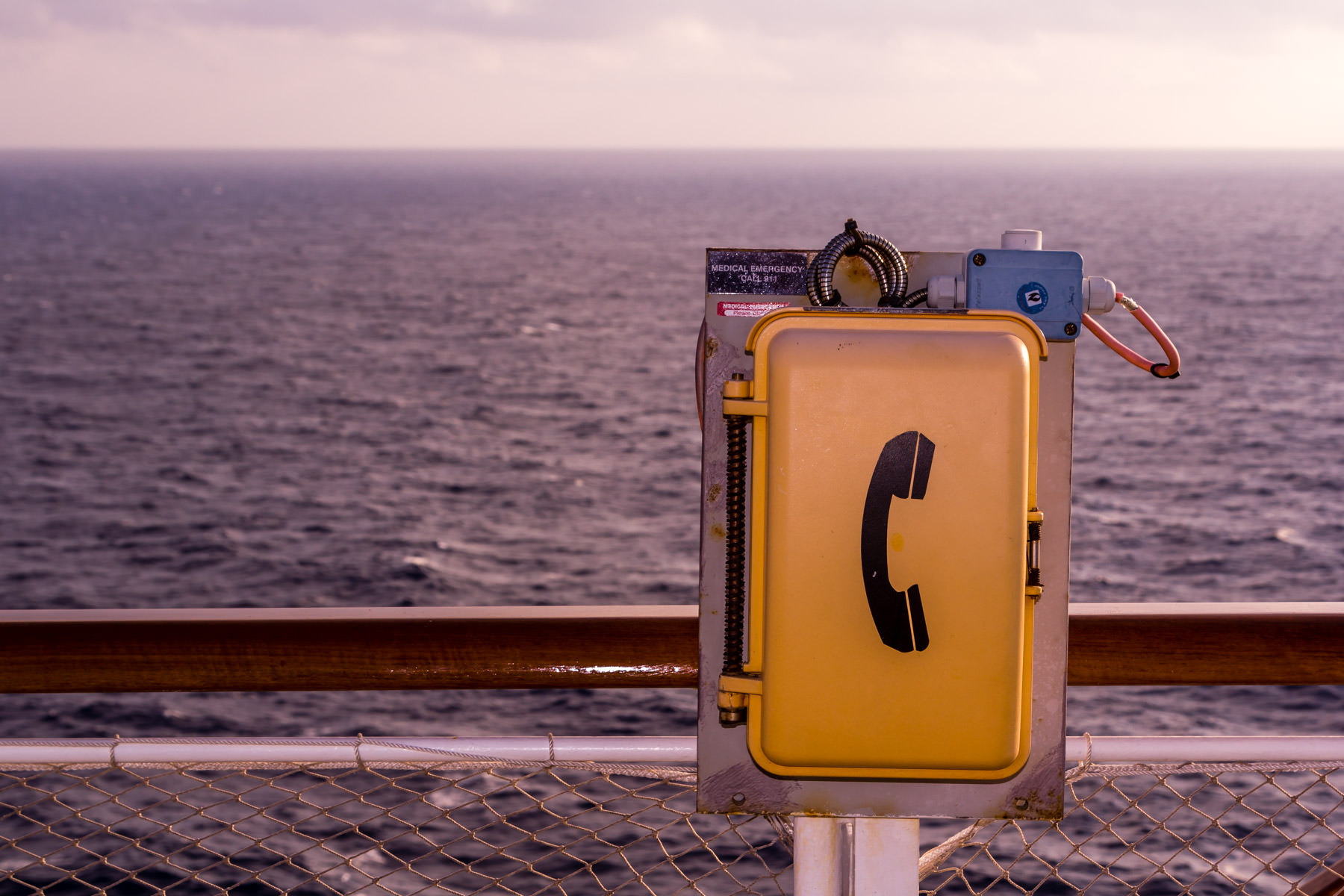 A shipboard telephone box mounted on a railing aboard the cruise ship Carnival Magic.