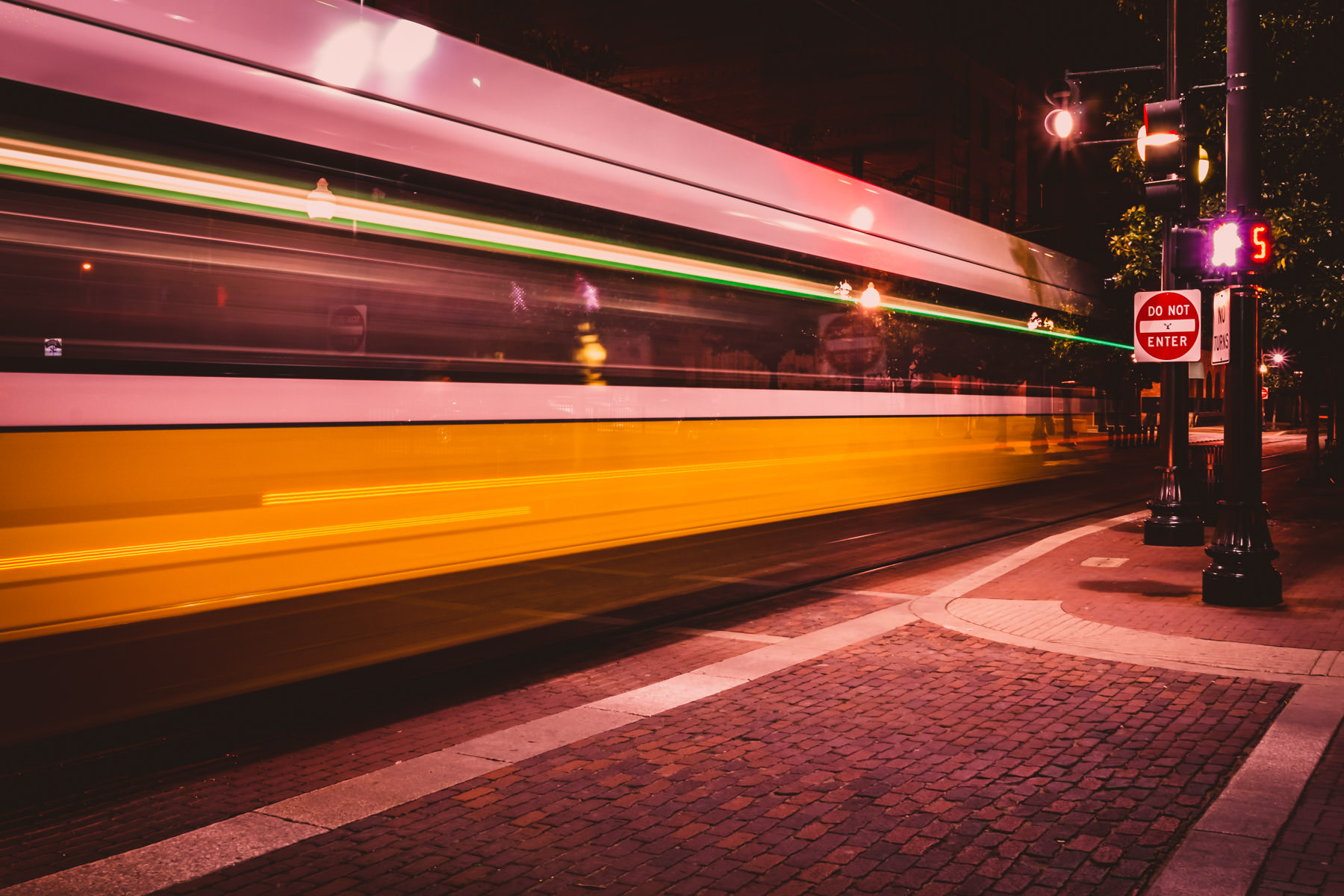 A long exposure shot of a DART Light Rail train speeding through Dallas' West End district.