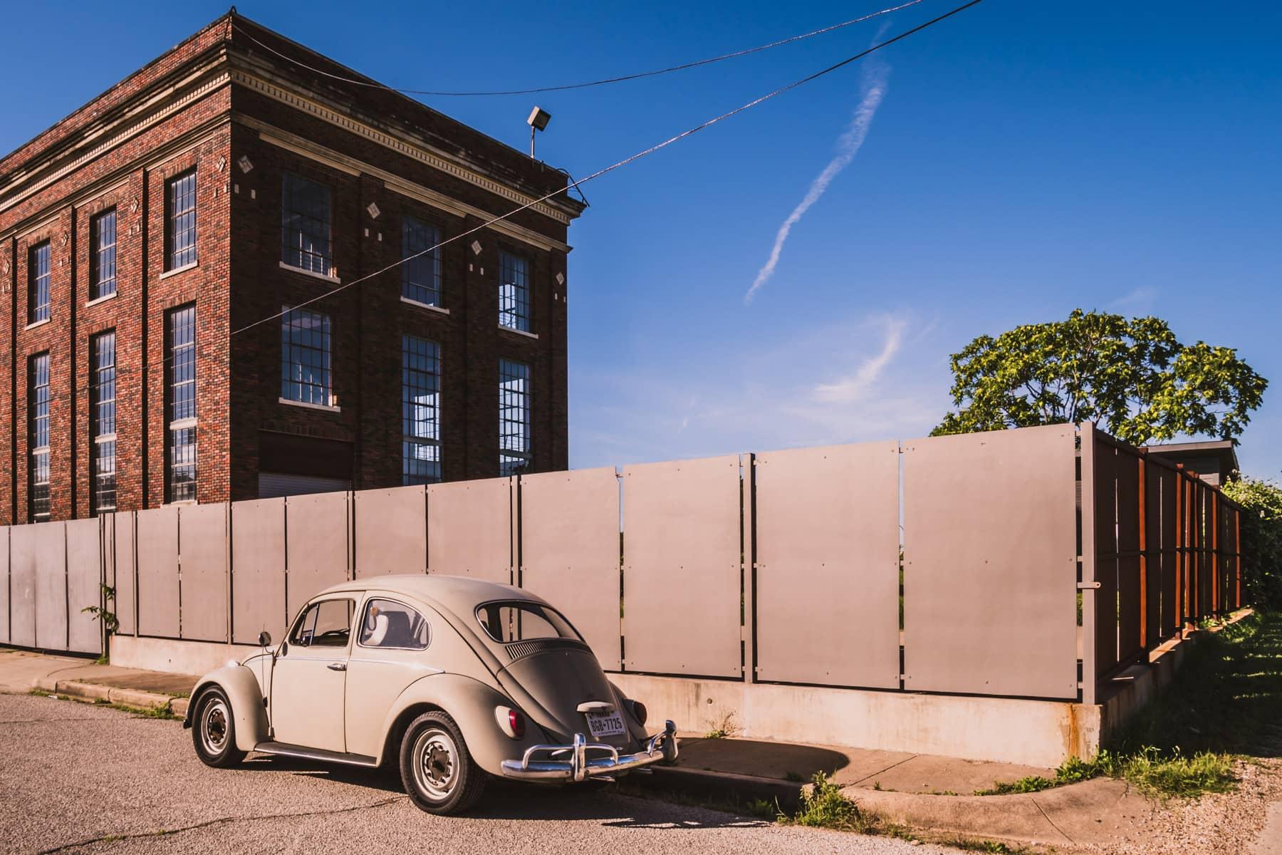 A classic Volkswagen Beetle, parked on a street in Dallas' Cedars Neighborhood near a historic Dallas Power & Light substation.