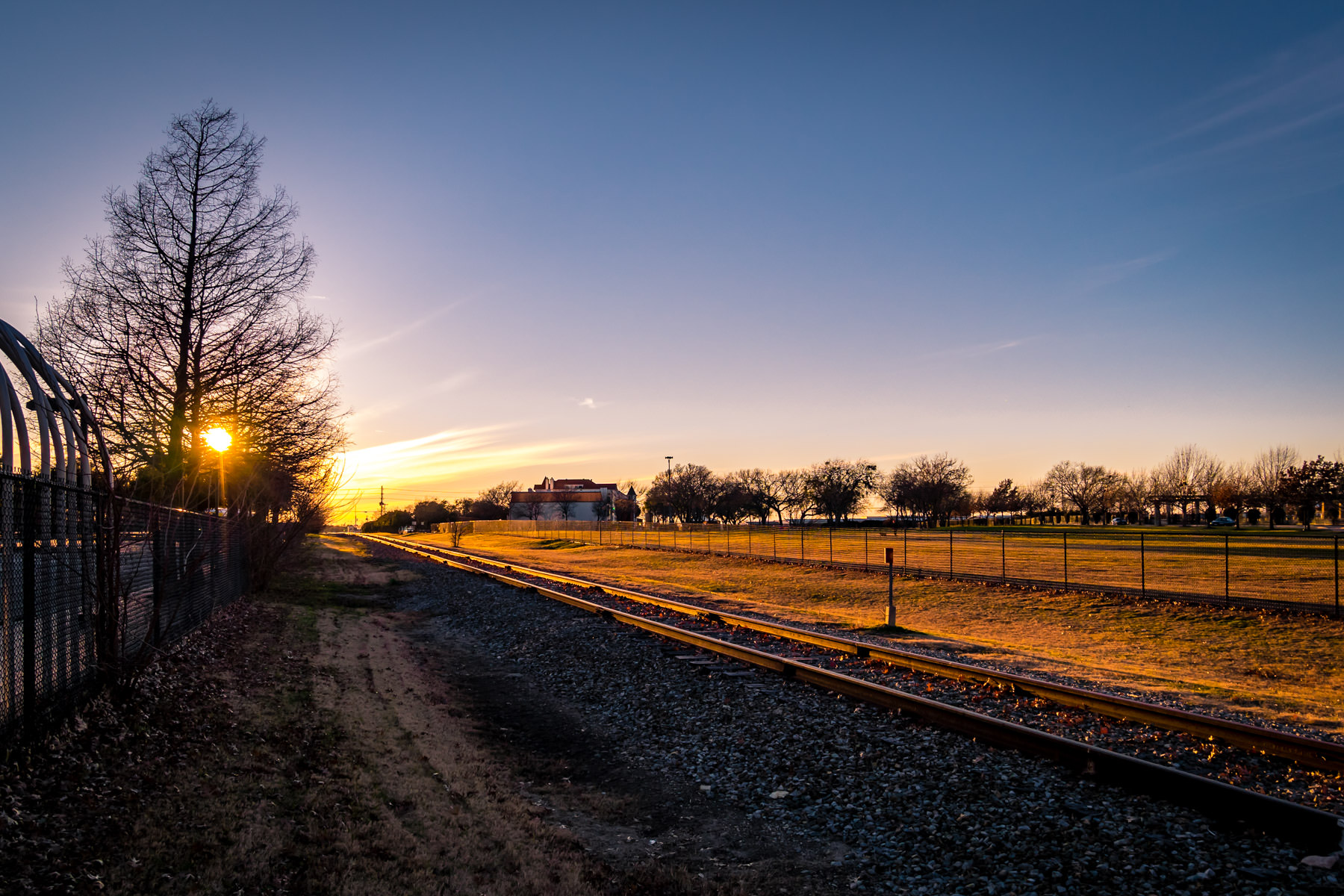 The evening sun illuminates train tracks running through Addison, Texas.