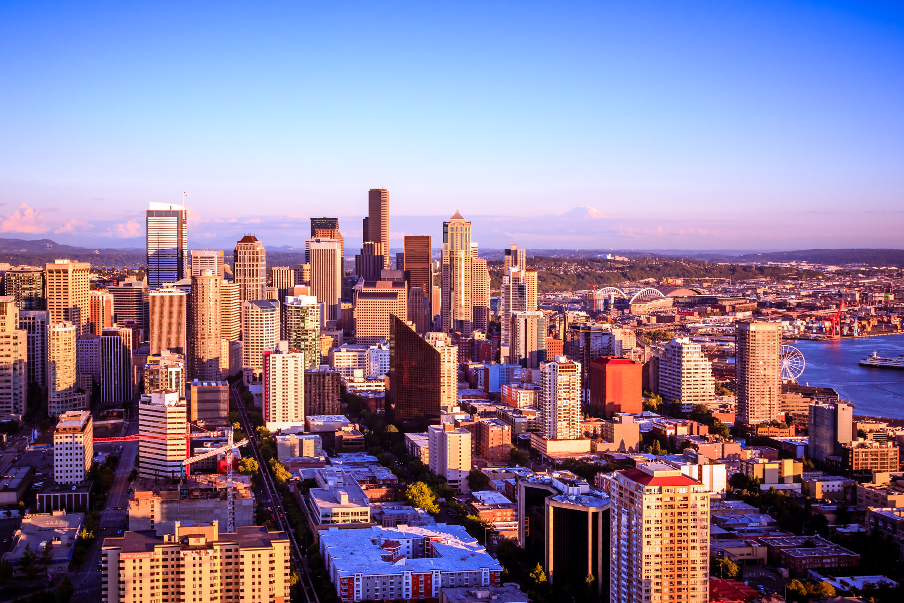 The evening sun illuminates Downtown Seattle, as seen from the Space Needle.