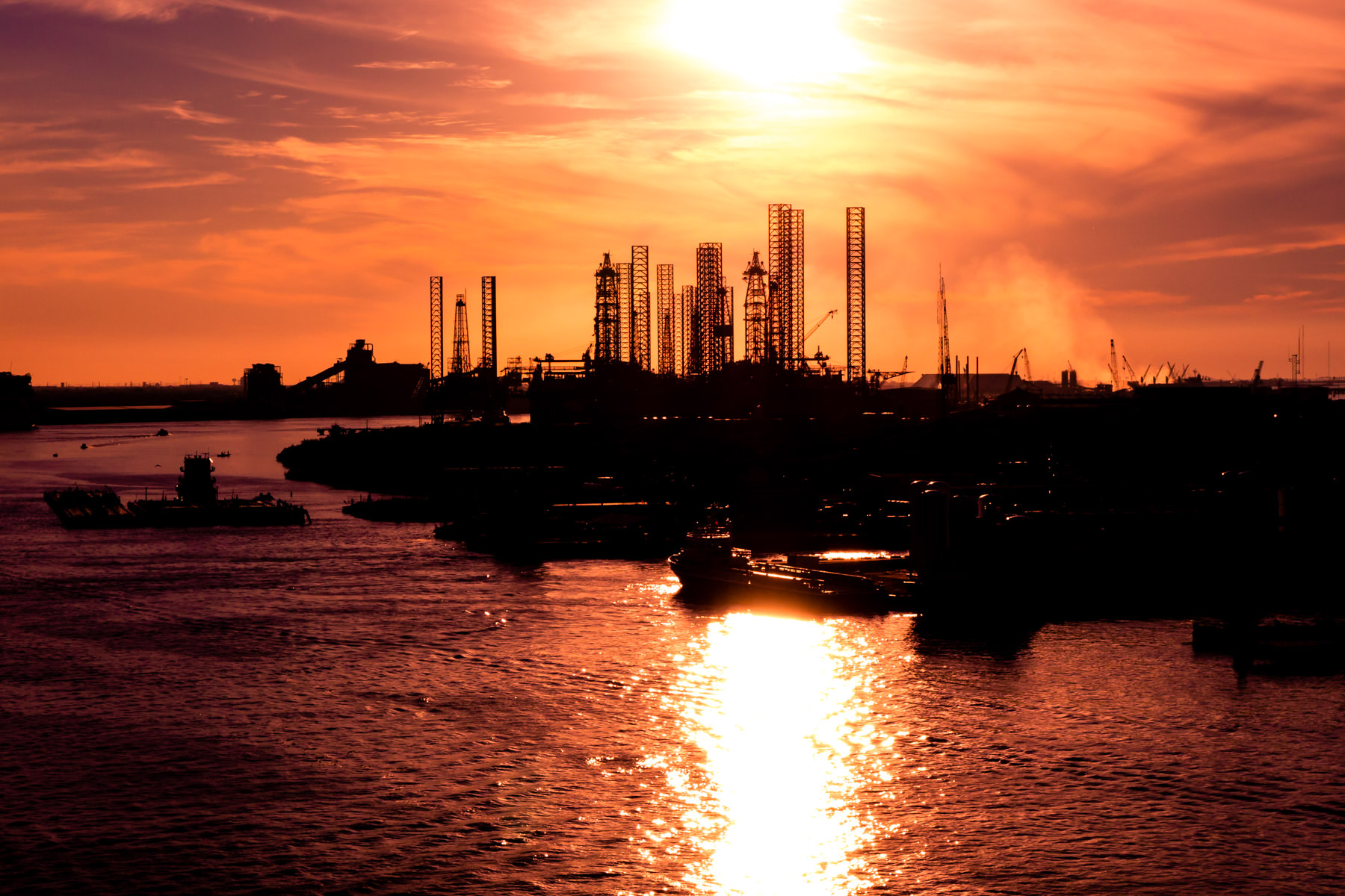 Steel legs on jack-up oil platforms in storage at Pelican Island rise into the sky as the sun begins to set on Galveston, Texas.