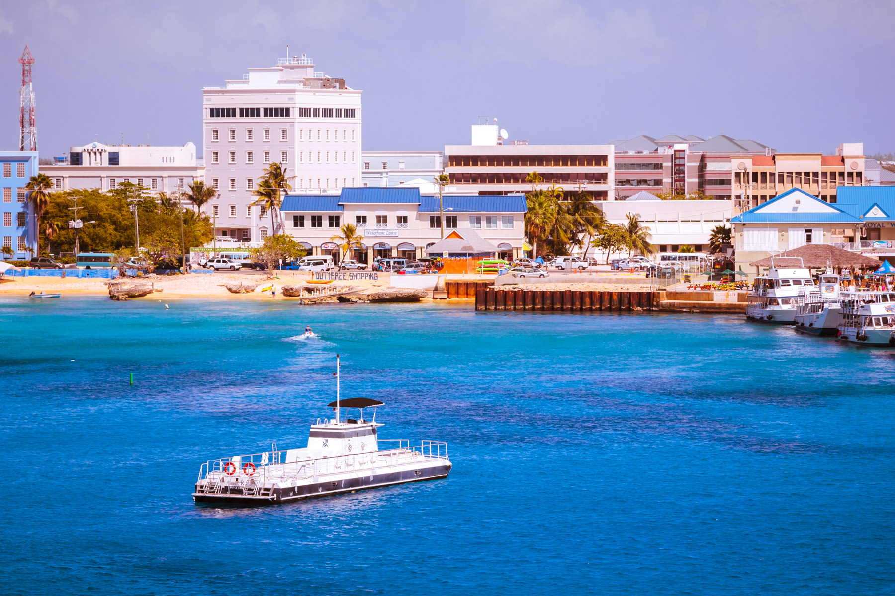 Low-slung buildings rise along the colorful coast of George Town, Grand Cayman.