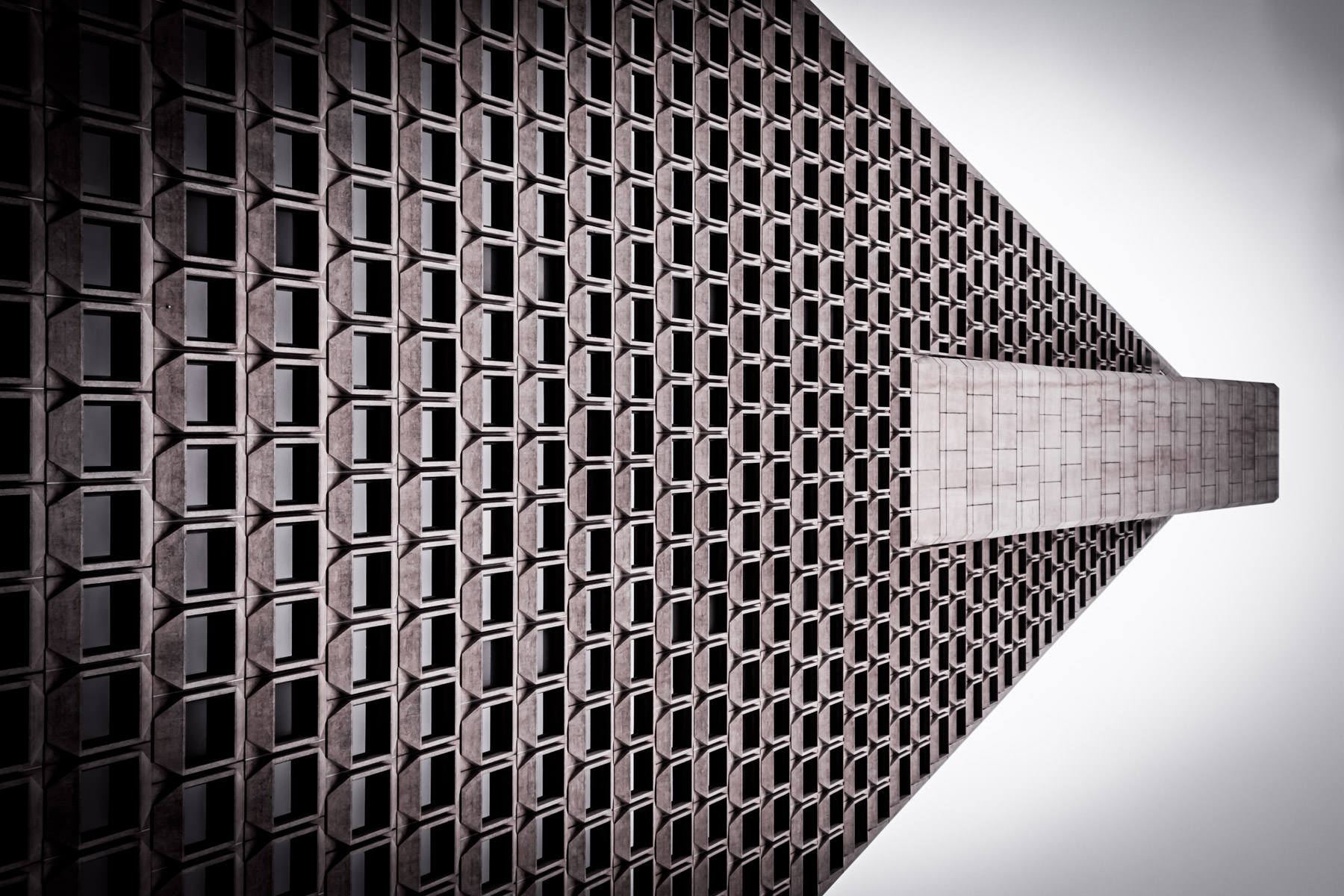 An abstracted study of the exterior of San Francisco's TransAmerica Pyramid as it rises into the overcast sky.