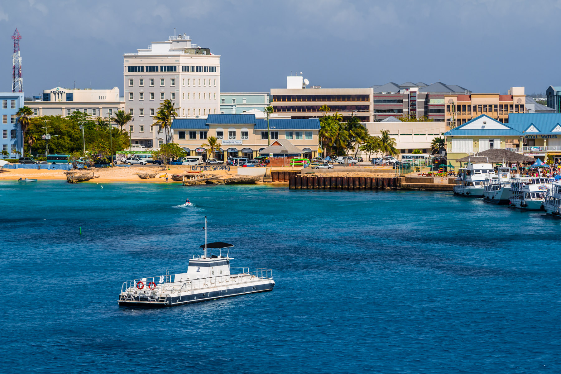 Low-slung buildings rise along the colorfulcoast of George Town, Grand Cayman.