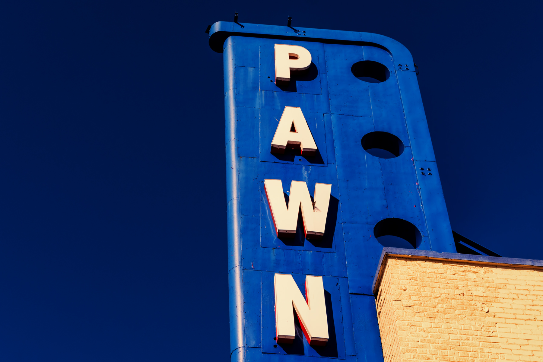 A pawn shop's sign rises into the blue North Texas sky in East Dallas.