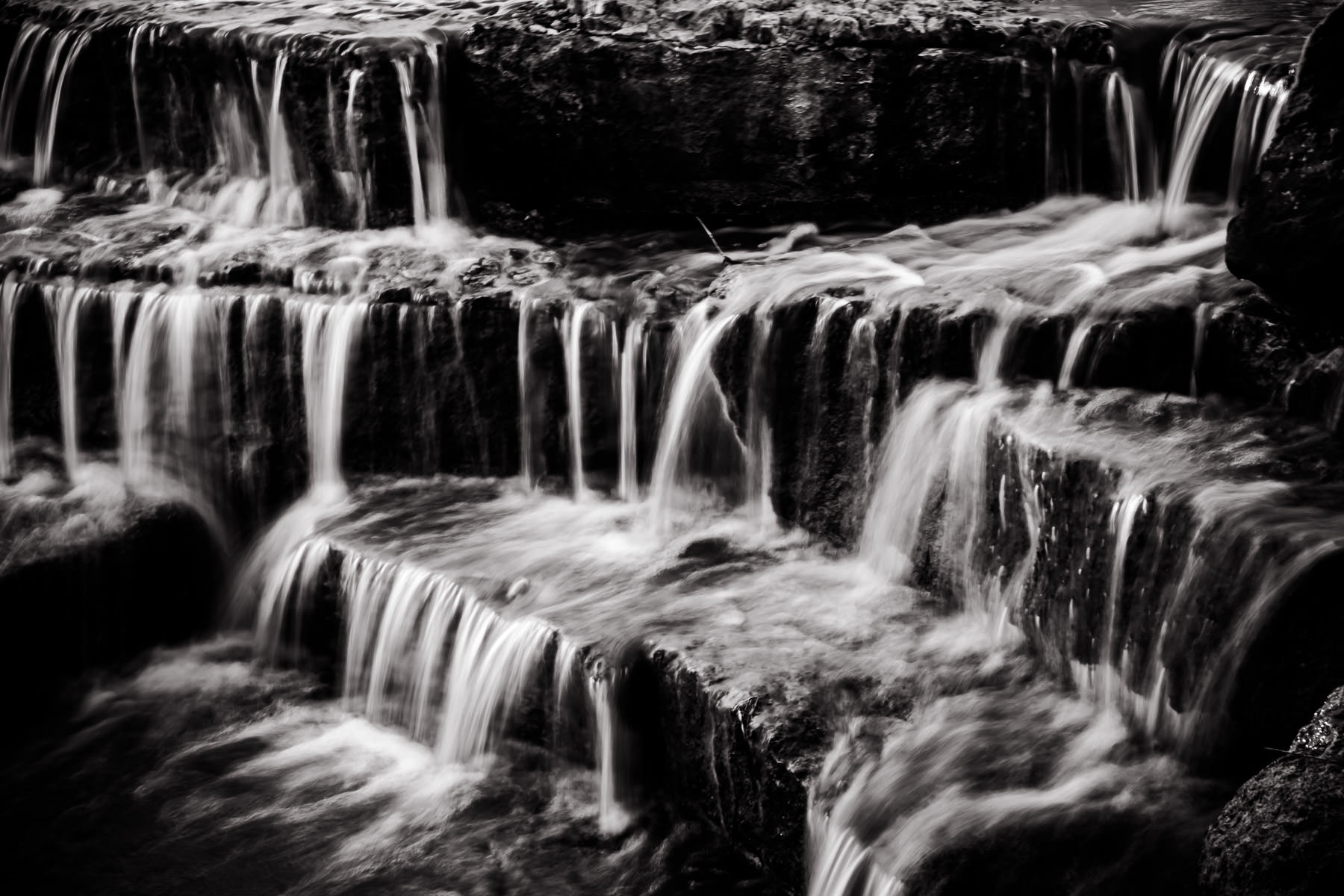 Water pours over rocks at a small waterfall in Frisco, Texas' Hall Office Park.