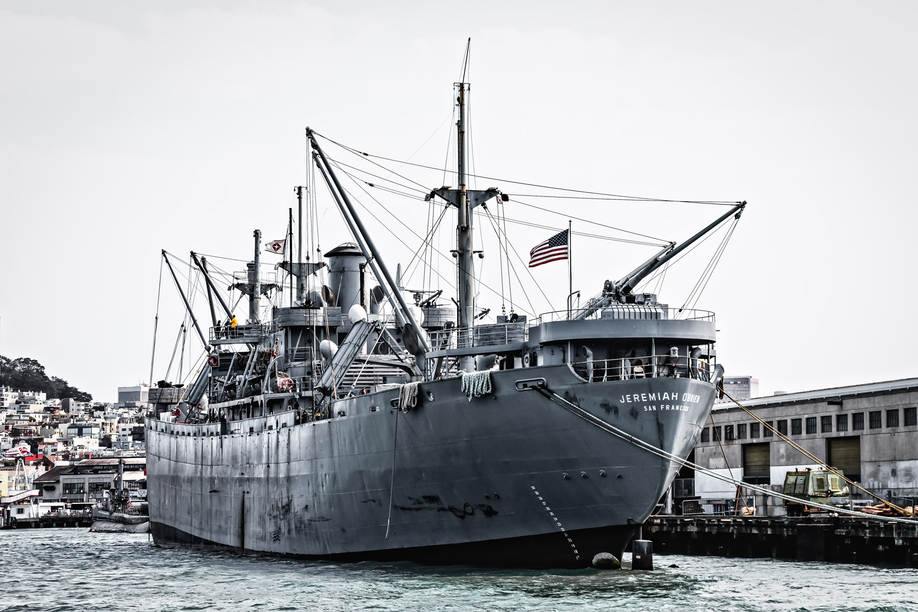 The SS Jeremiah O'Brien—one of only two surviving operational Liberty ships from World War II—docked at San Francisco's Pier 45 with the overcast city as its backdrop.