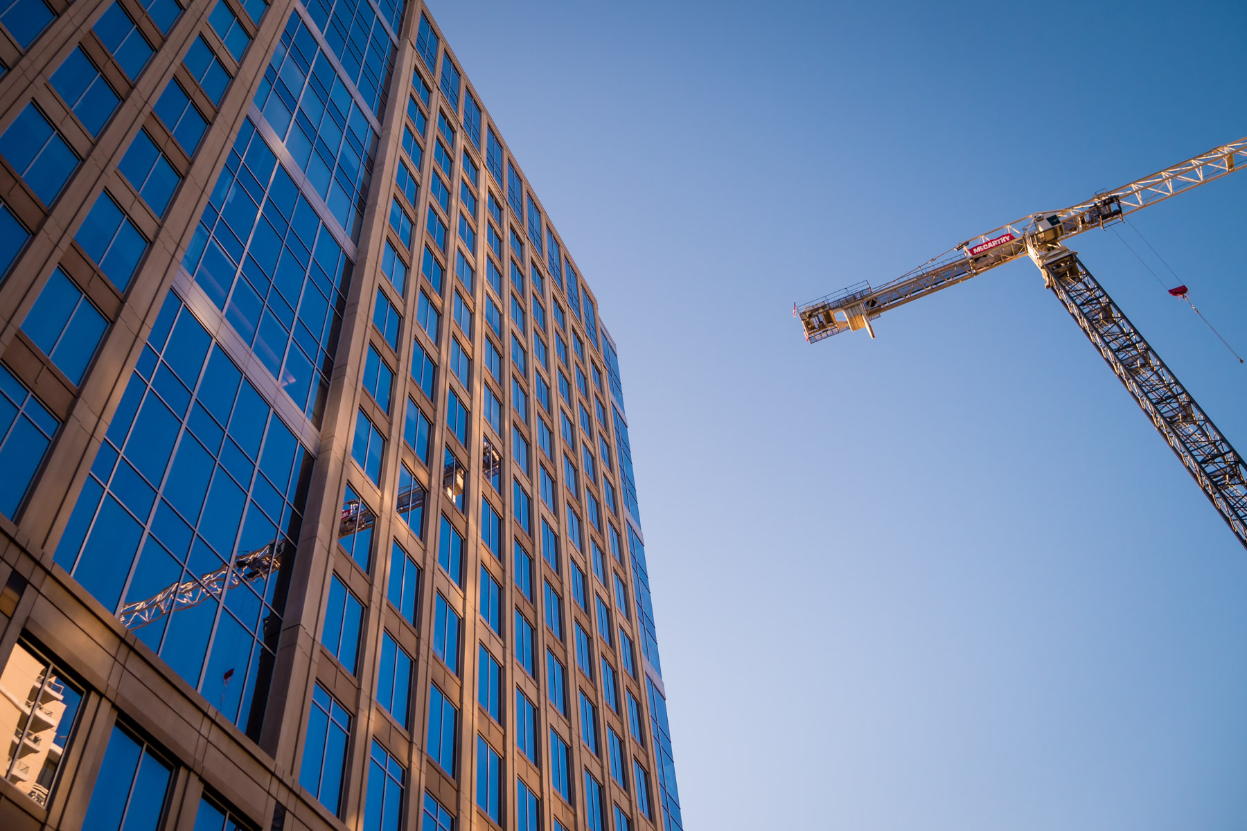 A tower crane is reflected in the glass façade of a nearby office building in Uptown Dallas.