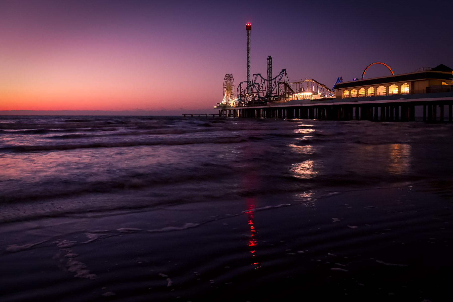 The first light of the day illuminates the Historic Pleasure Pier in Galveston, Texas.