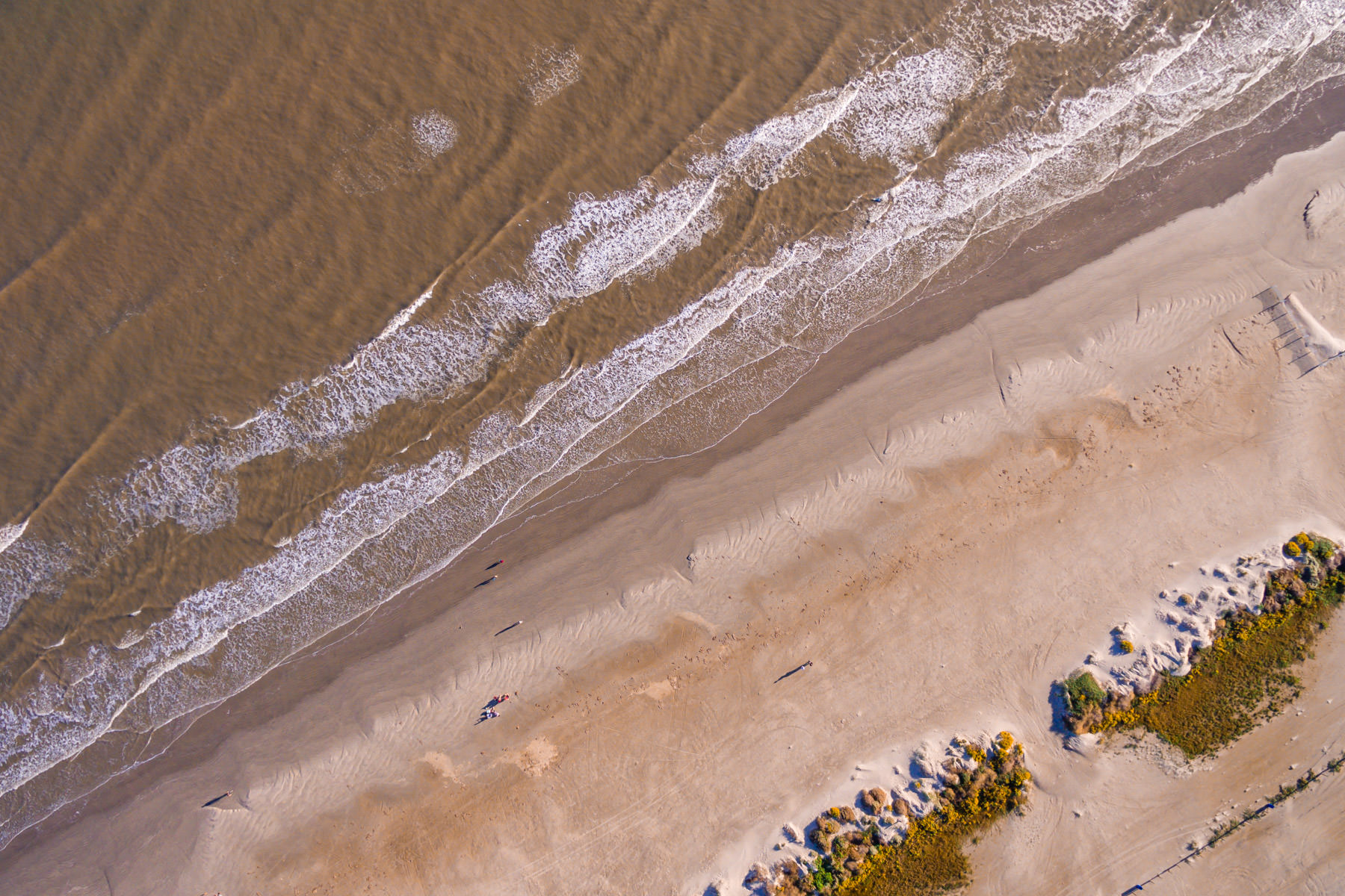 Waves crash onshore in an aerial shot of Galveston, Texas' East Beach.