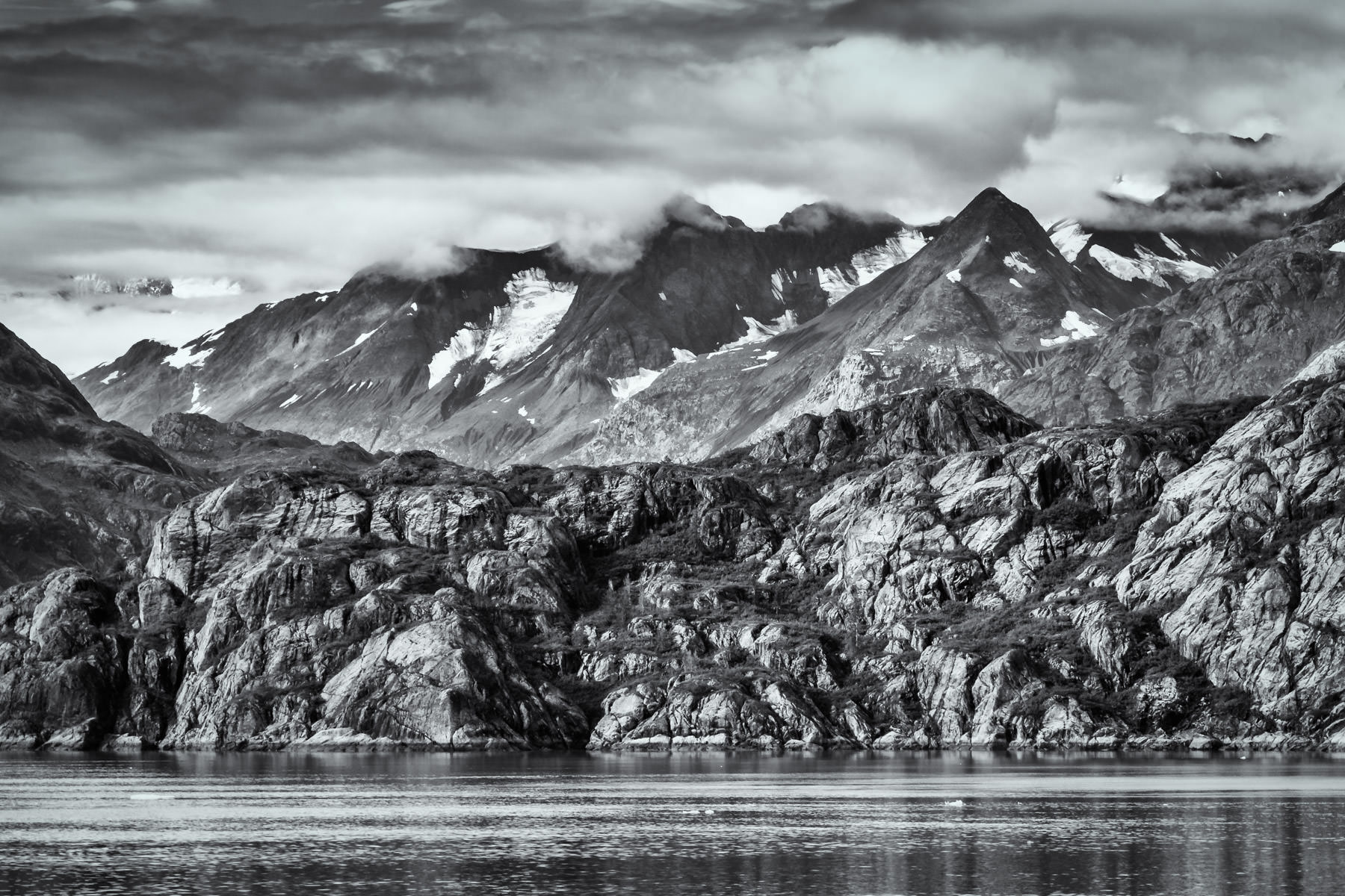Clouds obscure the peaks of mountains in Alaska's Glacier Bay National Park.