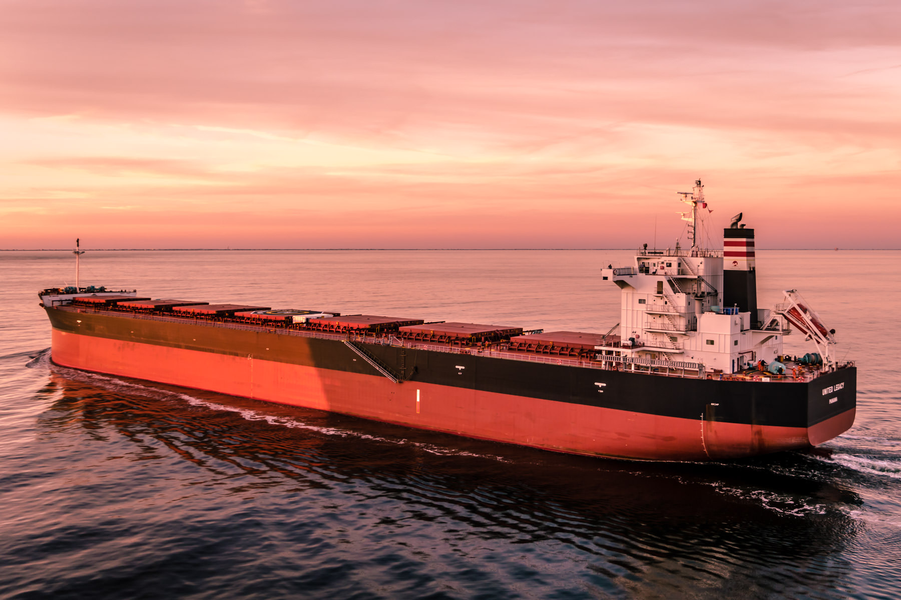 The bulk carrier United Legacy transits Bolivar Roads just off the coast of Galveston, Texas, as the sun sets on the Gulf of Mexico.