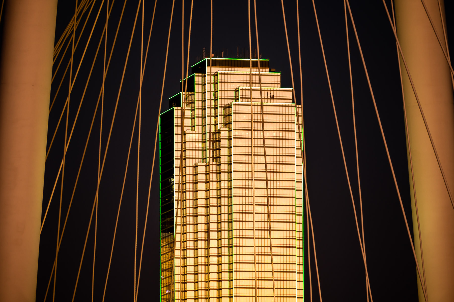 The last light of the day illuminates Downtown Dallas' Bank of America Plaza, as seen through the cables of the nearby Margaret Hunt Hill Bridge.