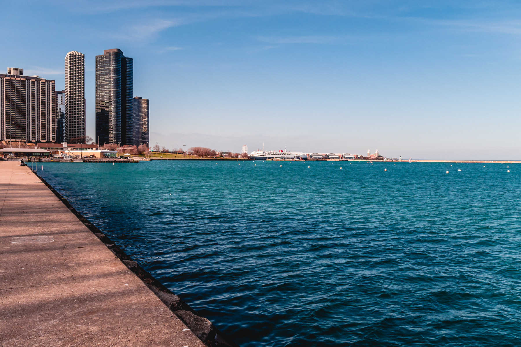 Skyscrapers, including Lake Point Tower, rise along the shore of Chicago's Monroe Harbor while nearby Navy Pier reaches out into Lake Michigan.