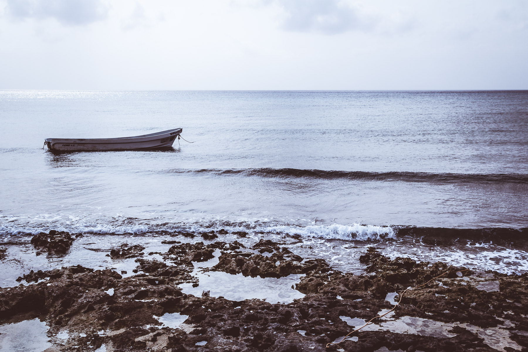 A small boat floats just offshore of a rocky beach at Cozumel, Mexico.