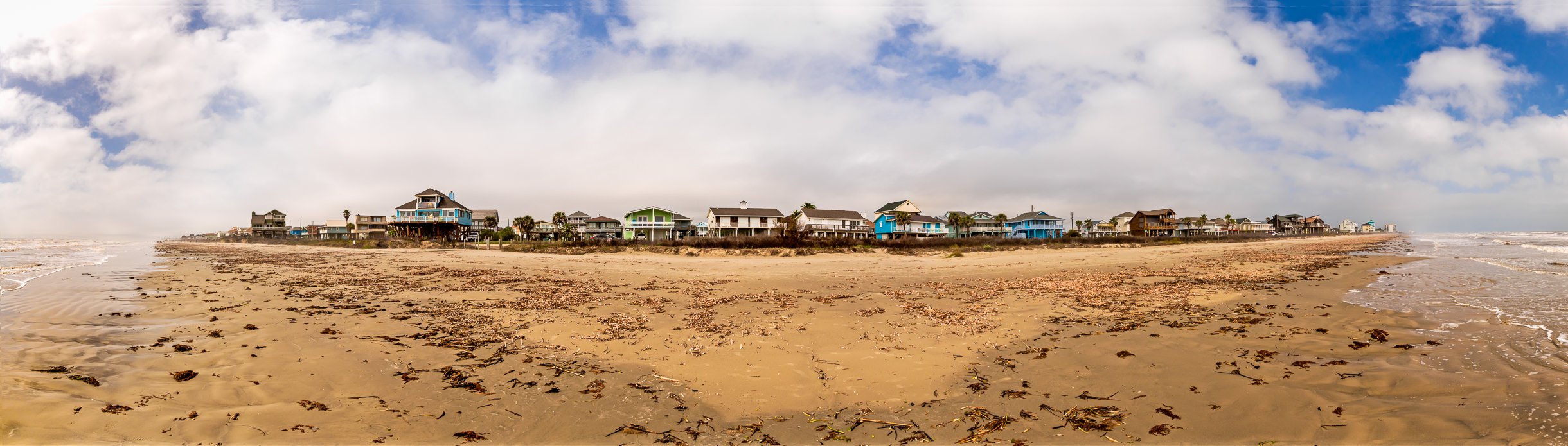 Beach houses line the seaweed-covered sandy beach at Galveston, Texas.
