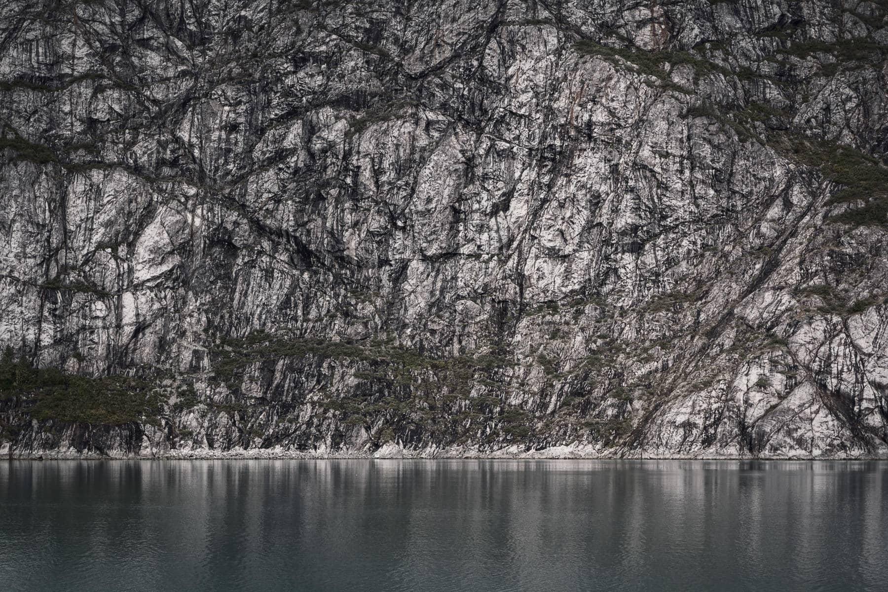 A sheer rock wall rises from the surface of Alaska's Glacier Bay.