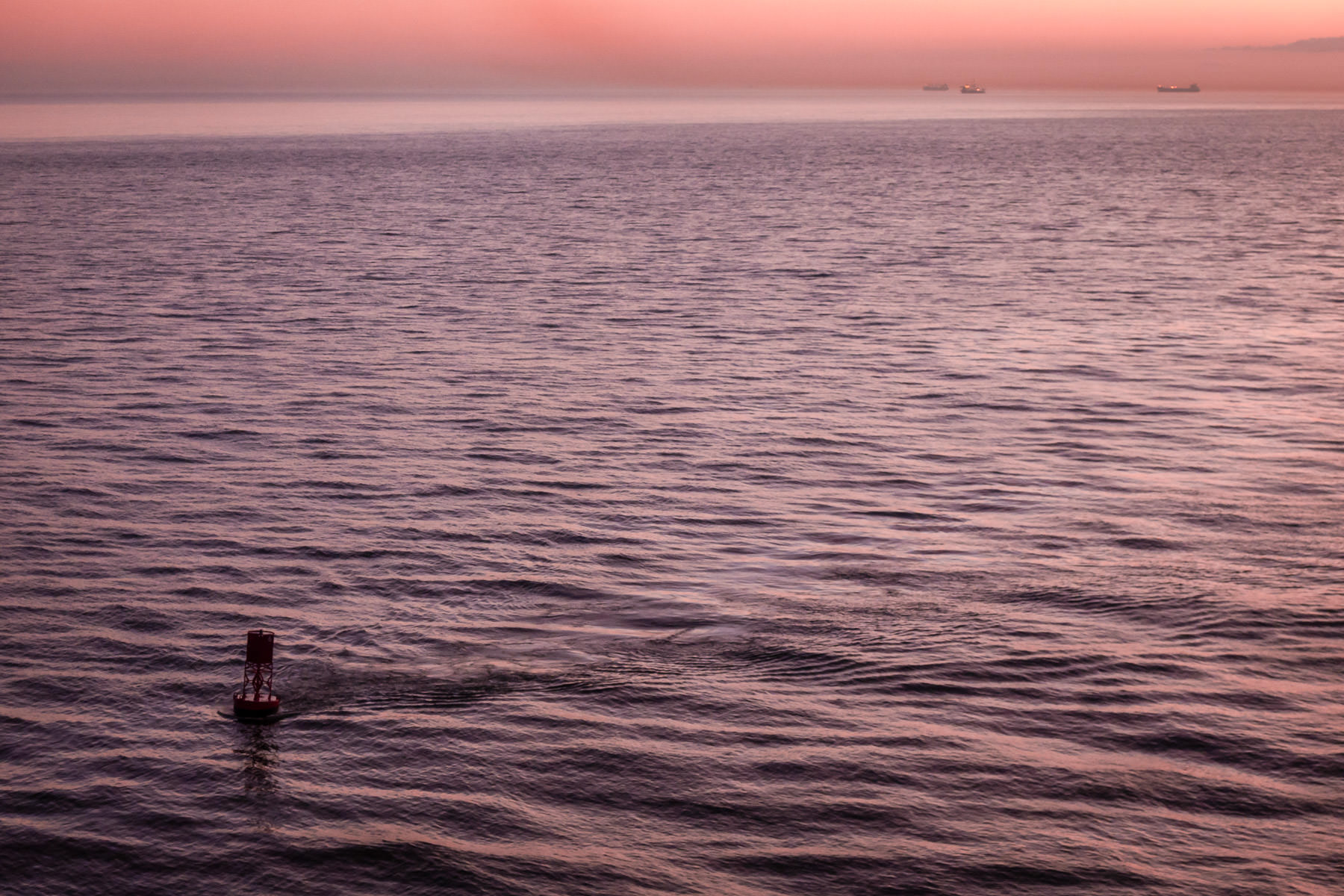 The early-morning sun illuminates a buoy marking the approach to Bolivar Roads—the entrance to Galveston Bay—near the north east end of Galveston Island, Texas.