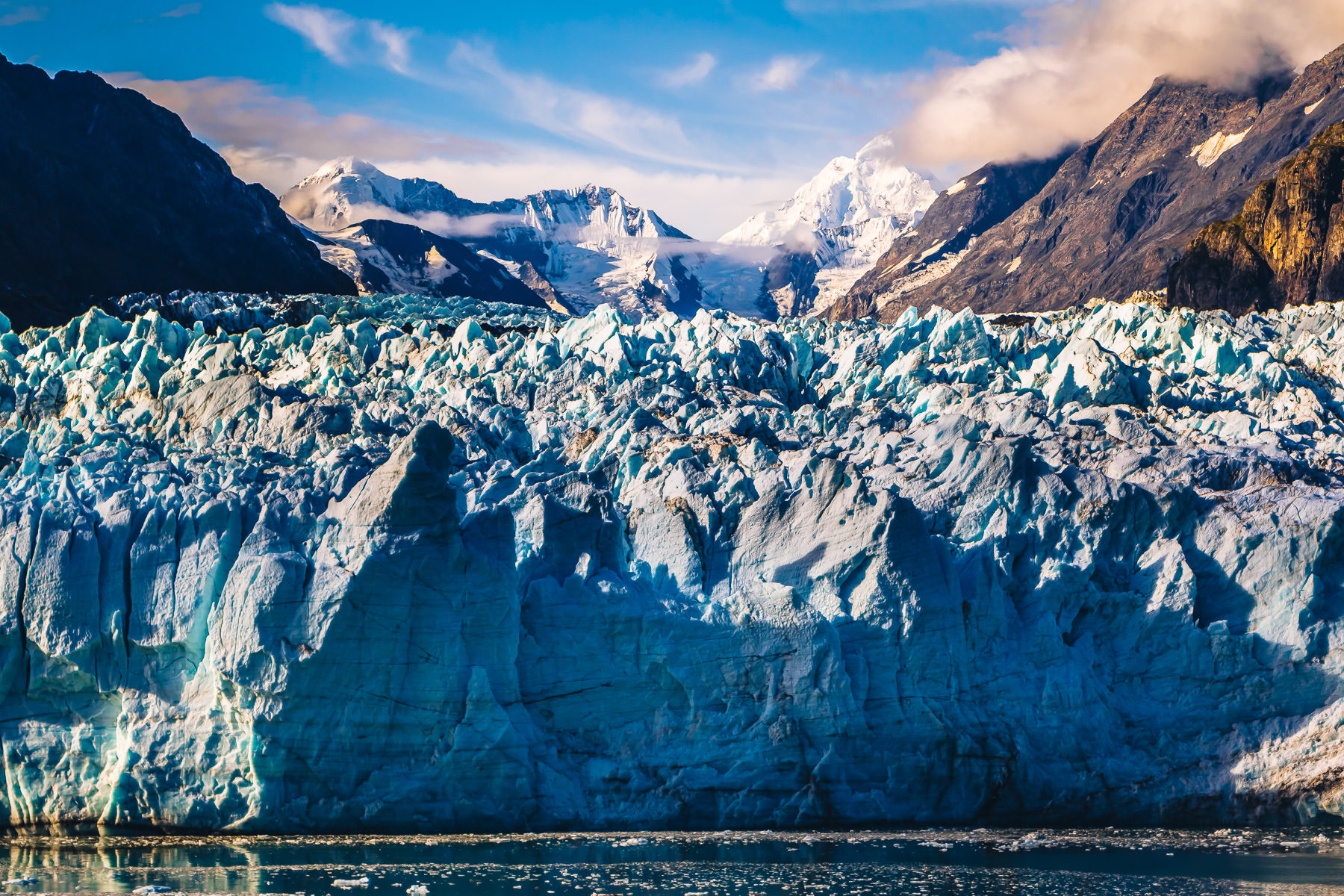 Distant mountains rise over the Margerie Glacier in Alaska's Glacier Bay National Park.