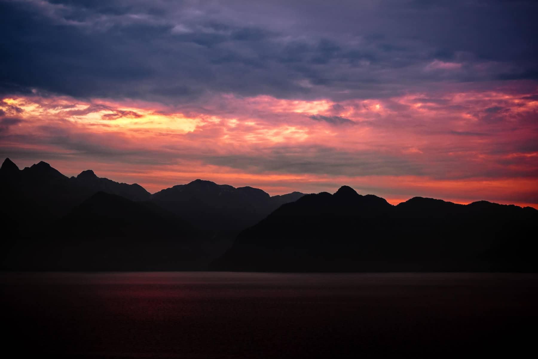 The morning sun silhouettes mountainous islands along Alaska's Stephens Passage.