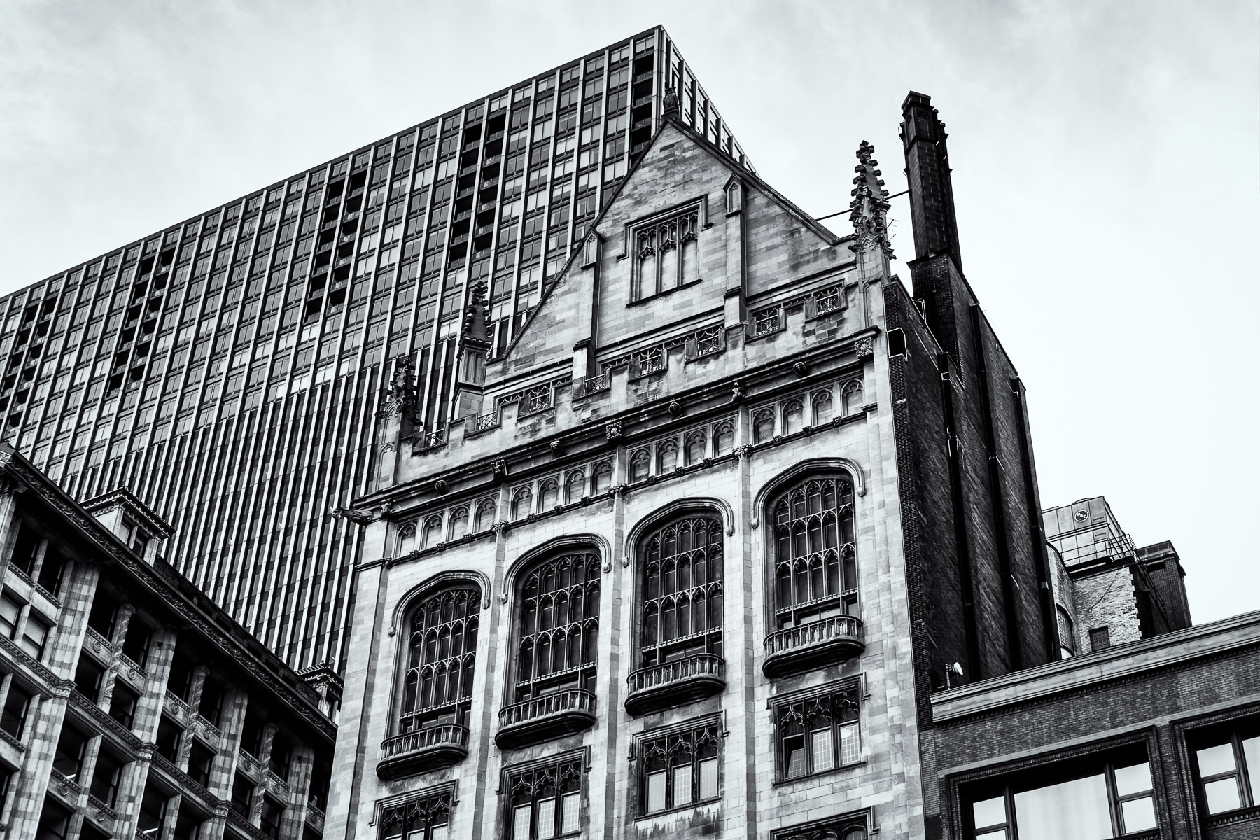 The gothic-styled University Club of Chicago building is dwarfed by the nearby Mid-Continental Plaza.