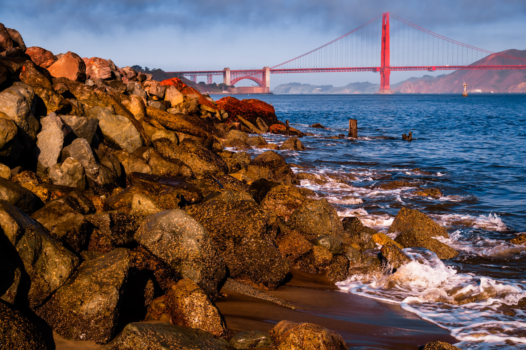 The San Francisco Bay surf laps at rocks on the beach at Crissy Field as the Golden Gate Bridge rises in the distance.